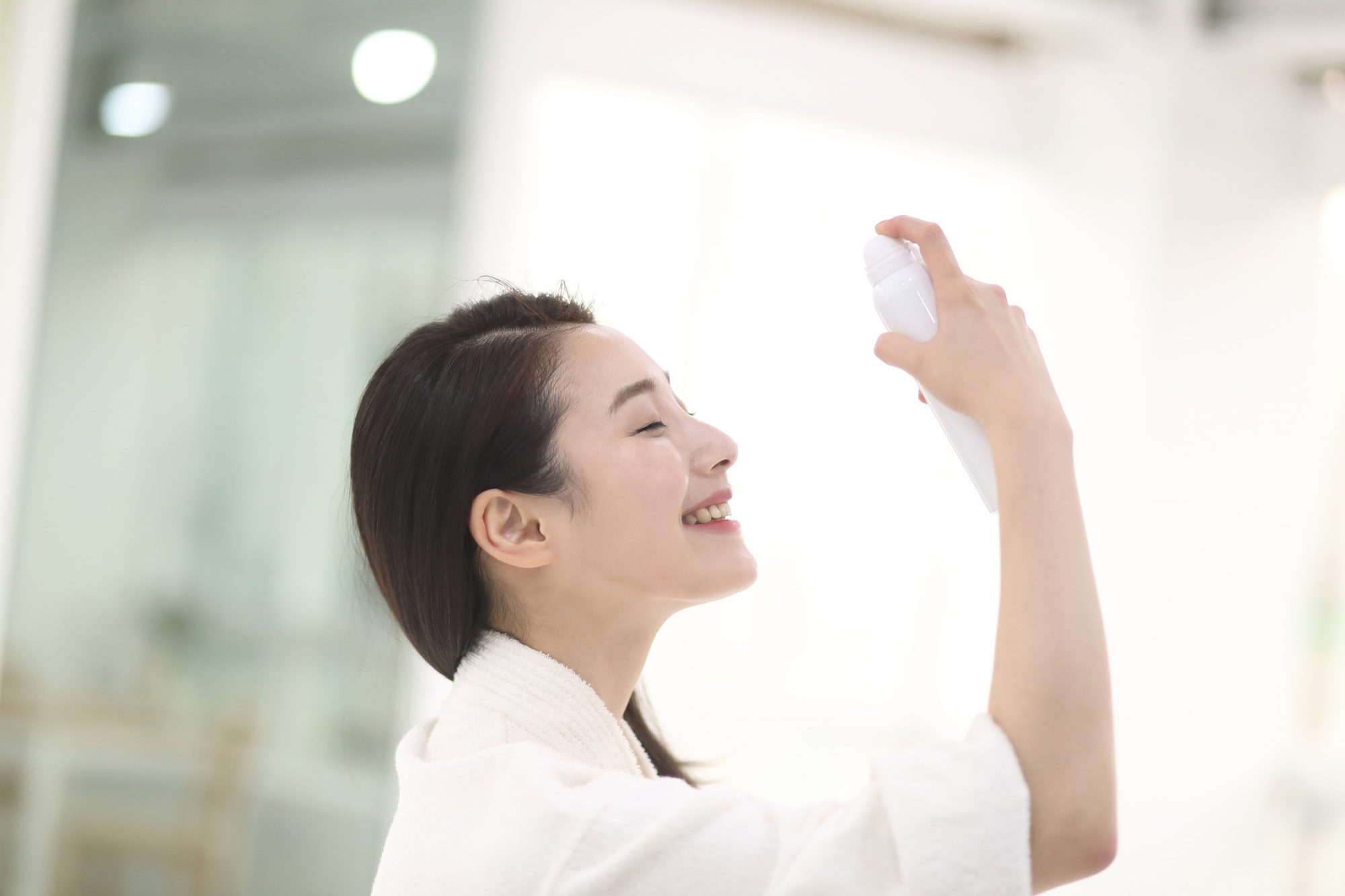 woman smiling spraying setting spray on her face