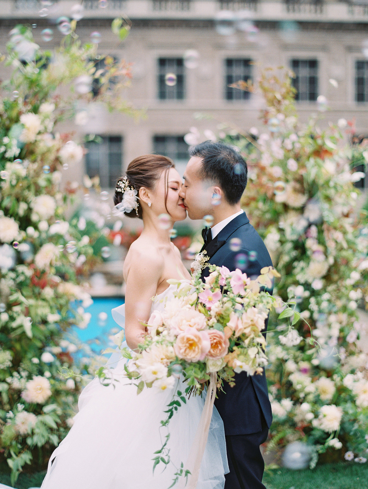 couple first kiss under floral arch