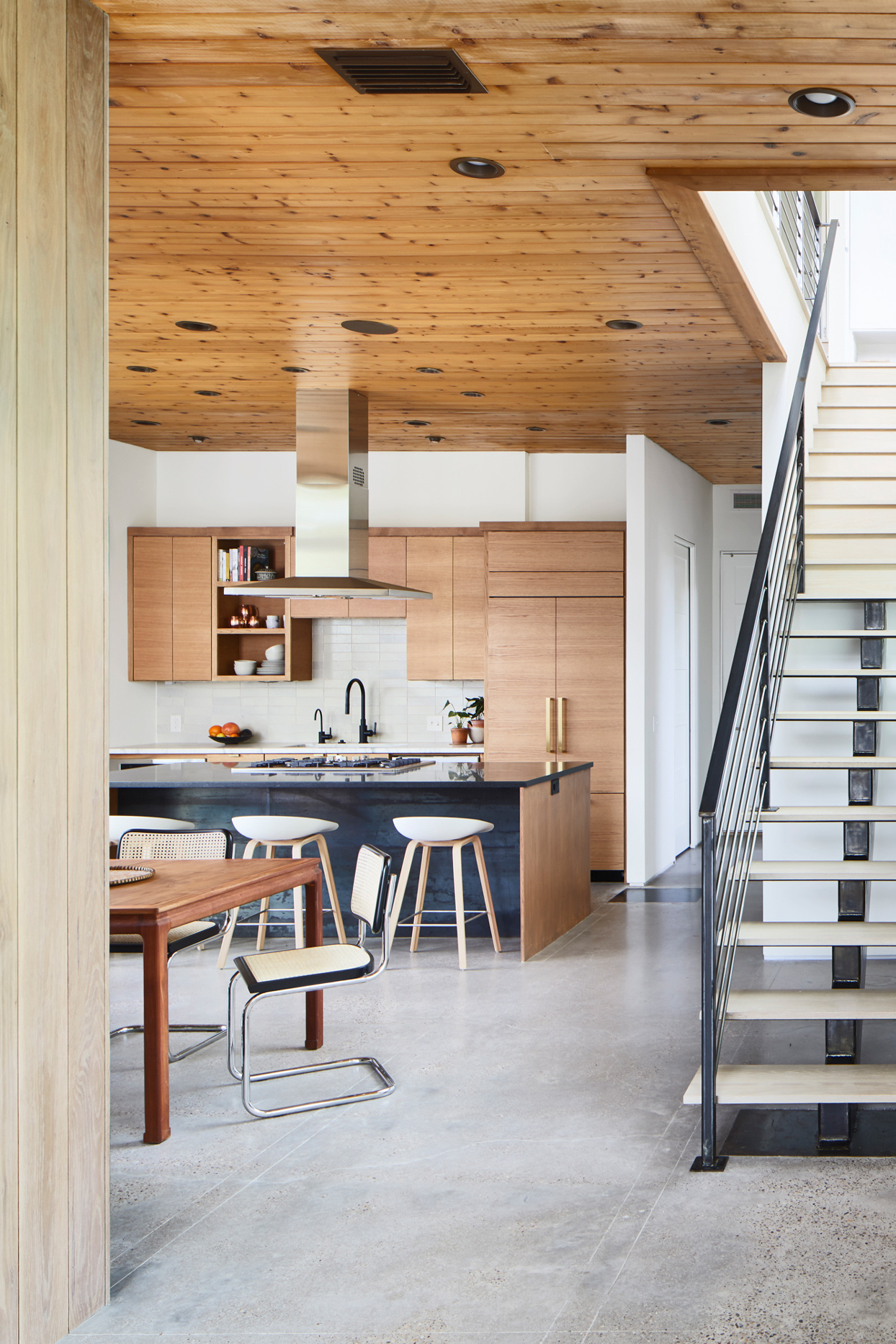 neutral-colored dining room and kitchen featuring floating treads staircase