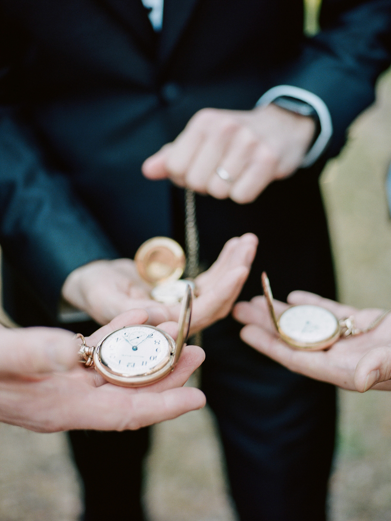 groomsmen holding classic pocket watches