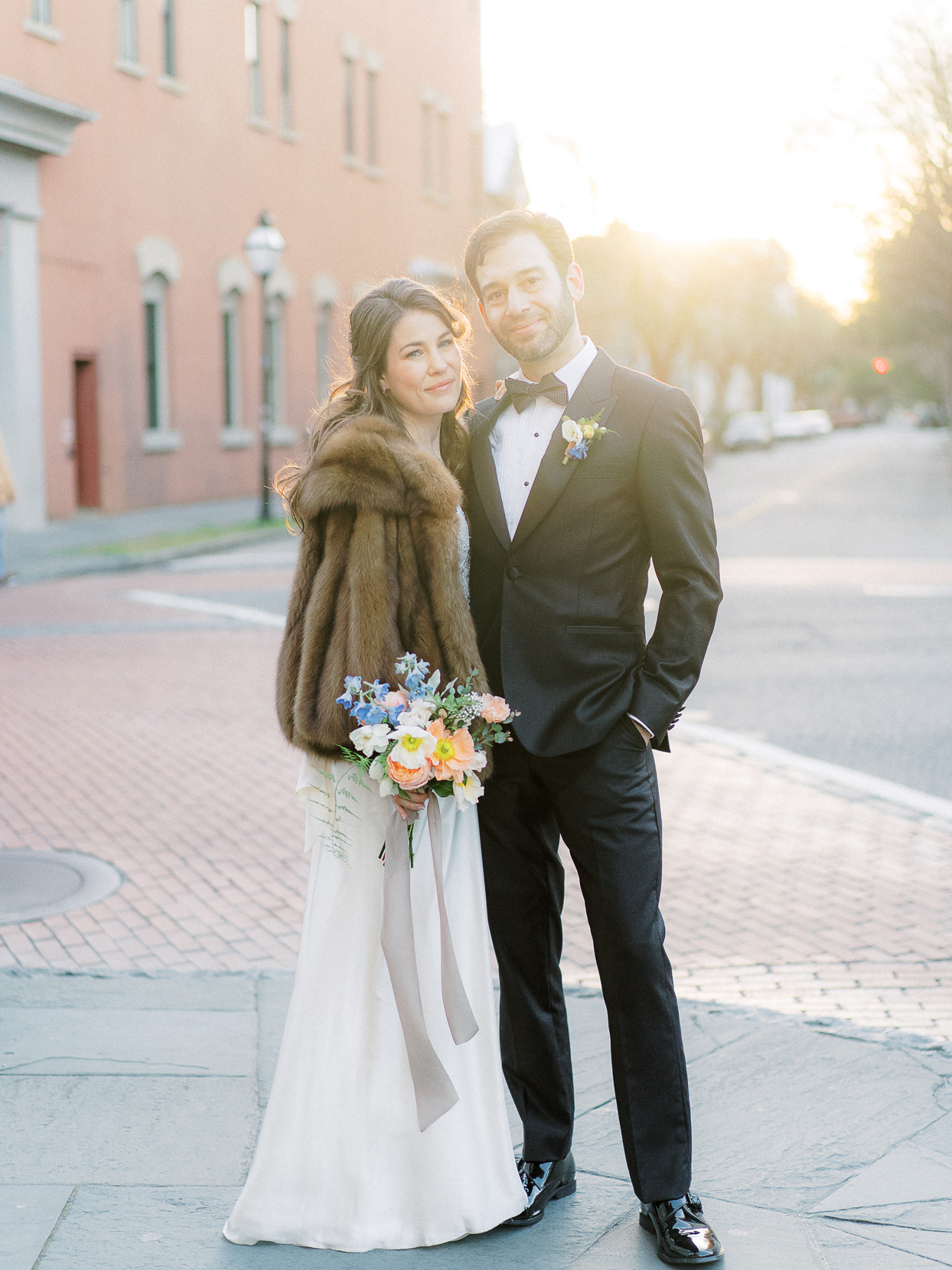 bride and groom outside on roadway smiling