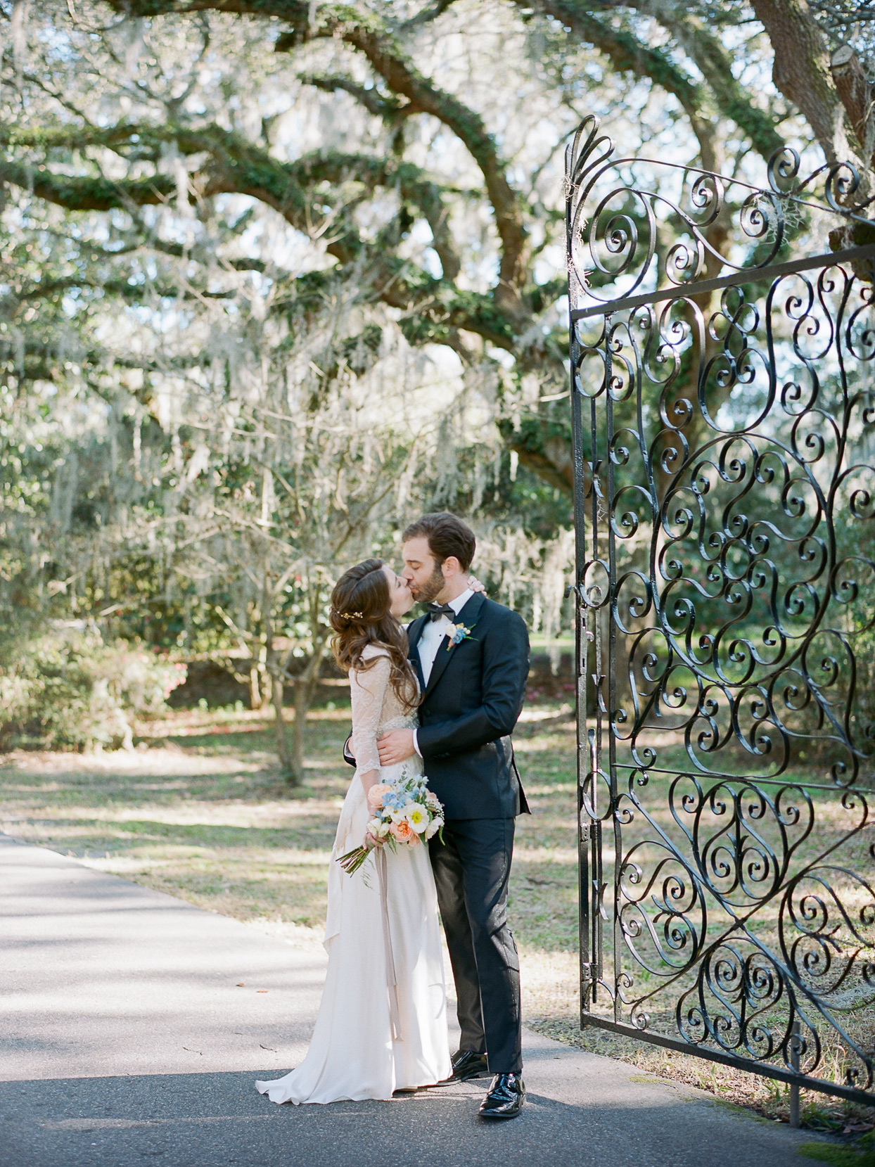 bride and groom kissing by iron gate outside