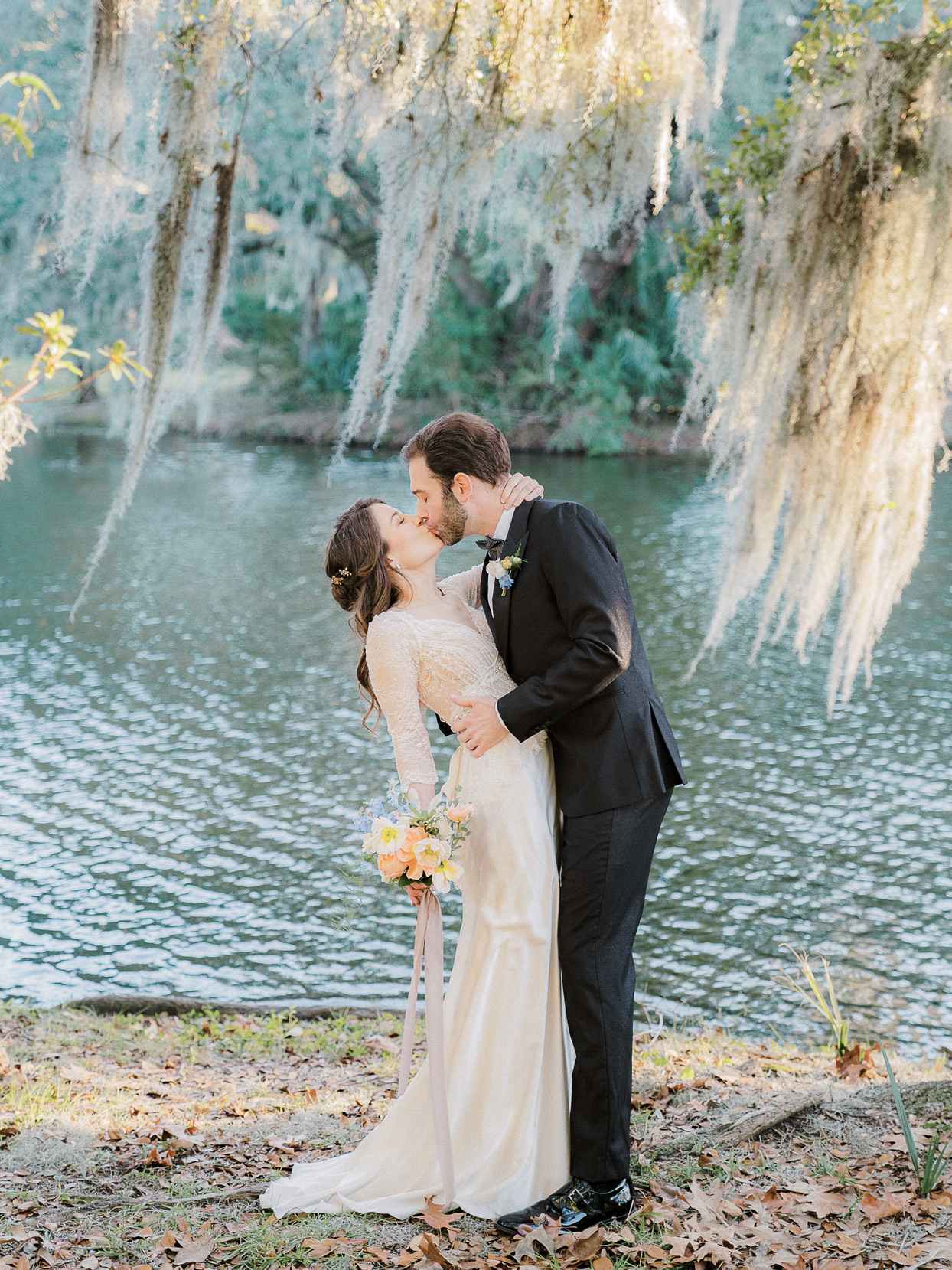bride and groom kissing under willow tree outside