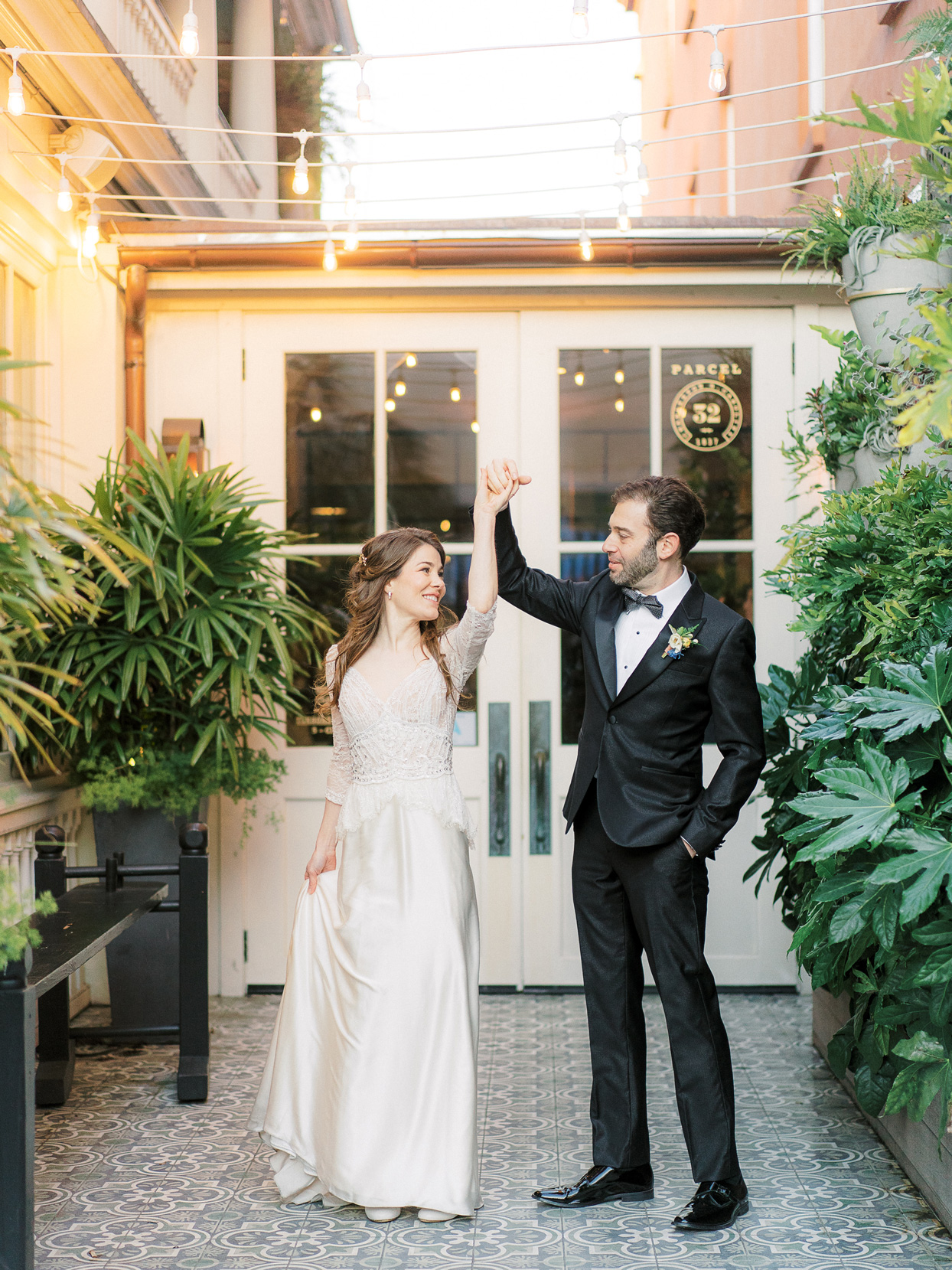 bride and groom hold hands smiling outside reception venue