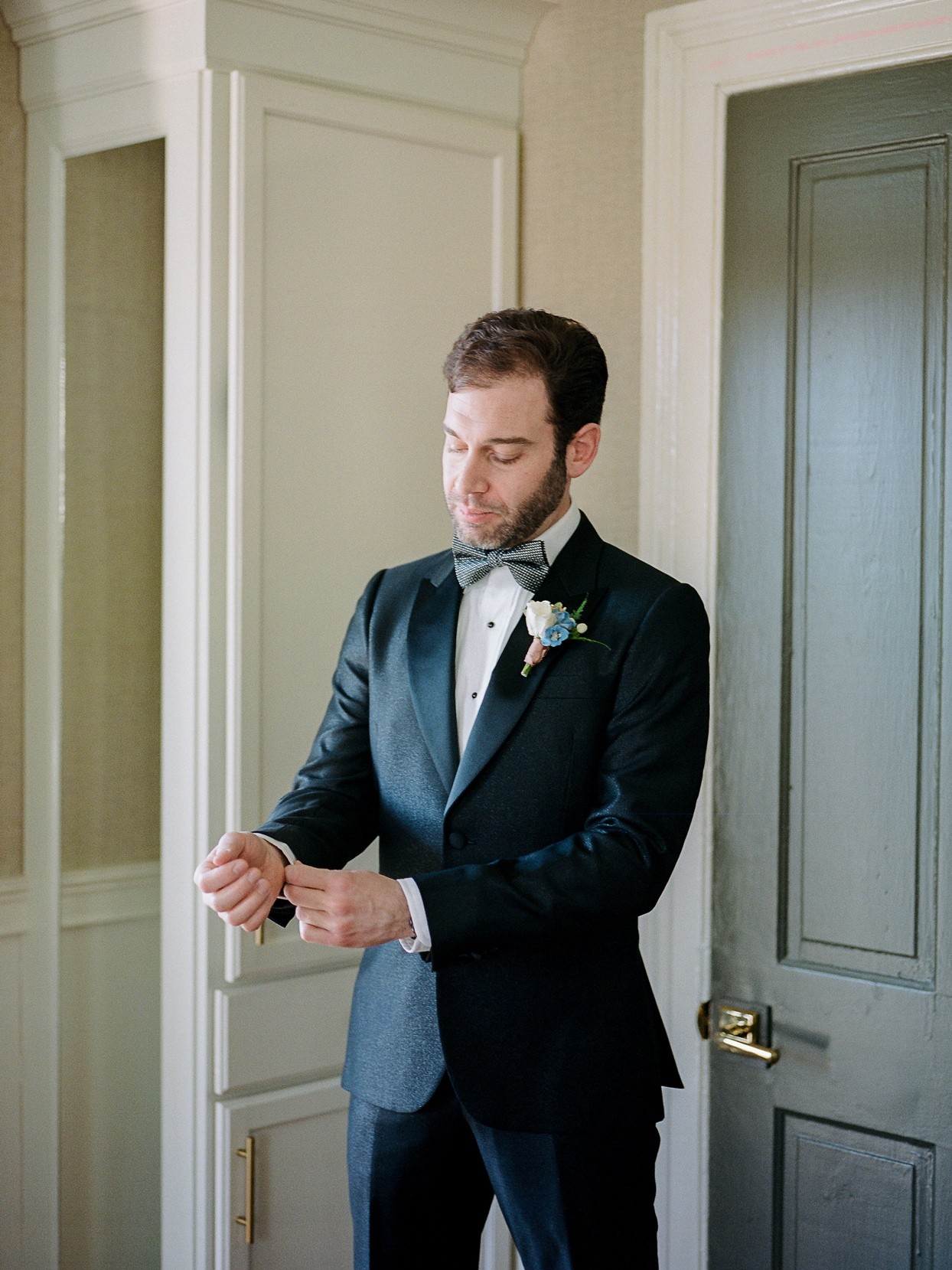 groom wearing traditional black suit with bow tie