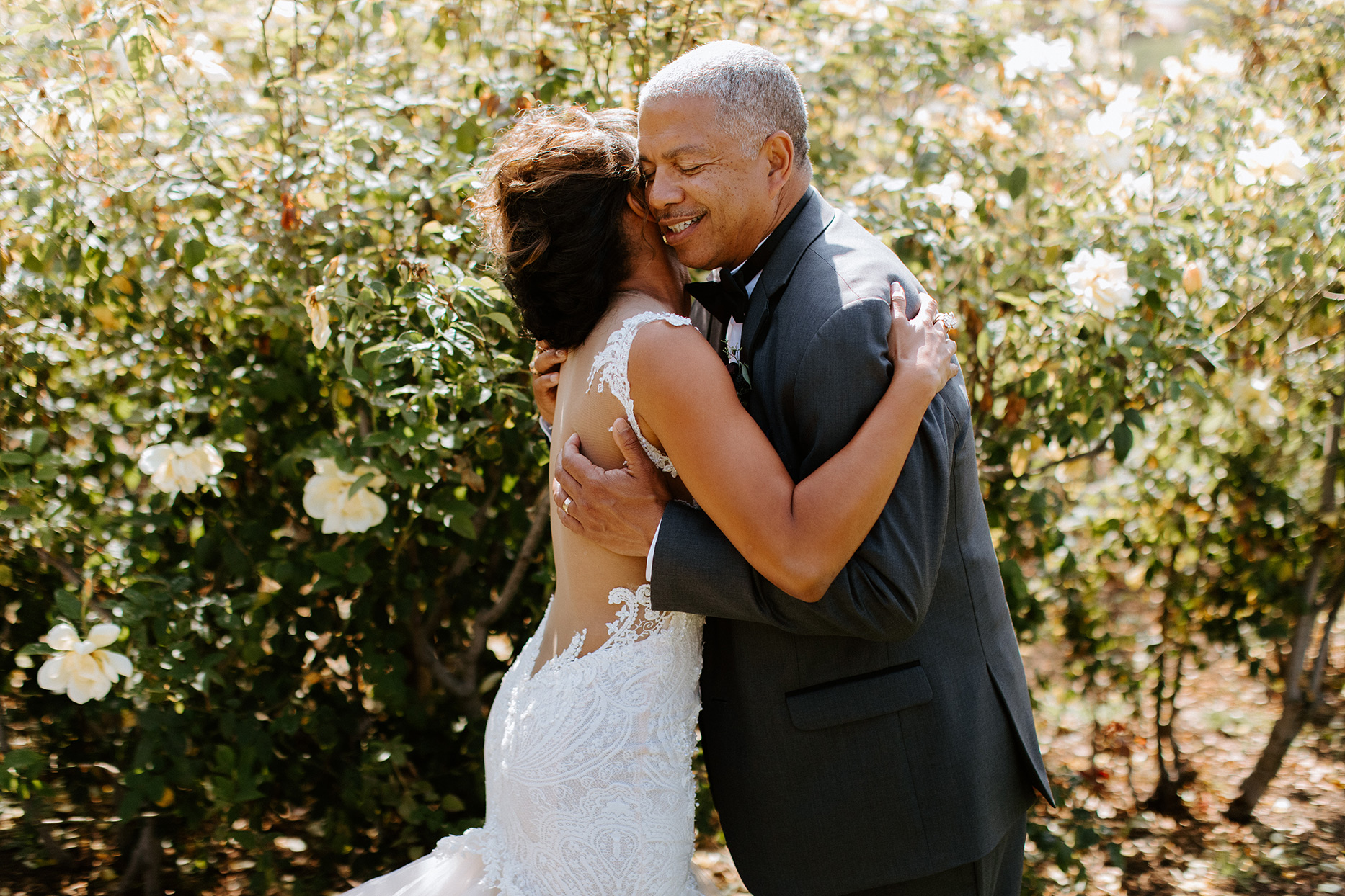bride hugging father in front of flowering bushes