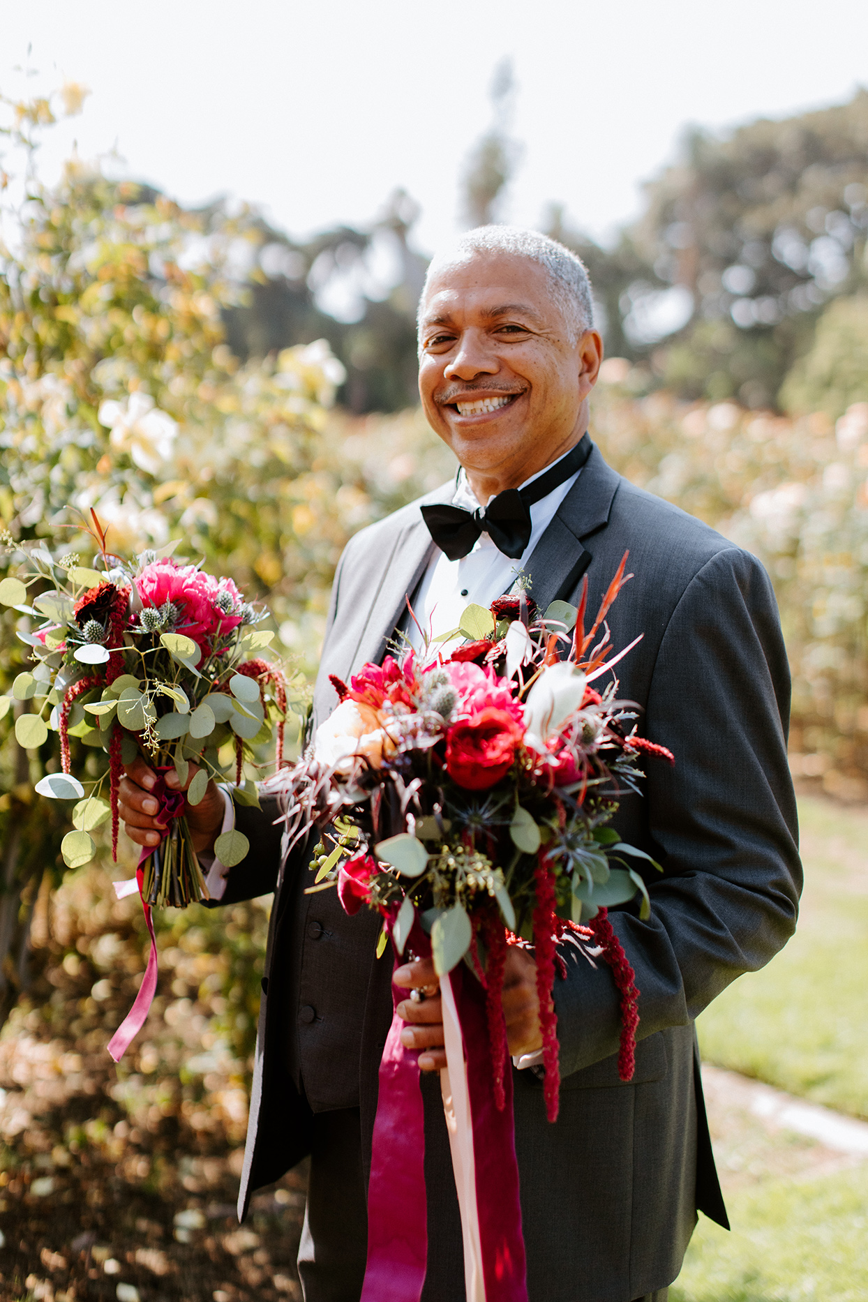 father of the bride holding jewel toned wedding bouquets