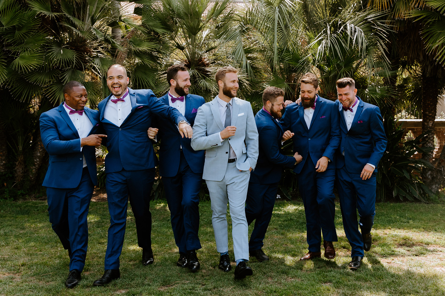 groom and groomsmen in blue suits in front of palm trees