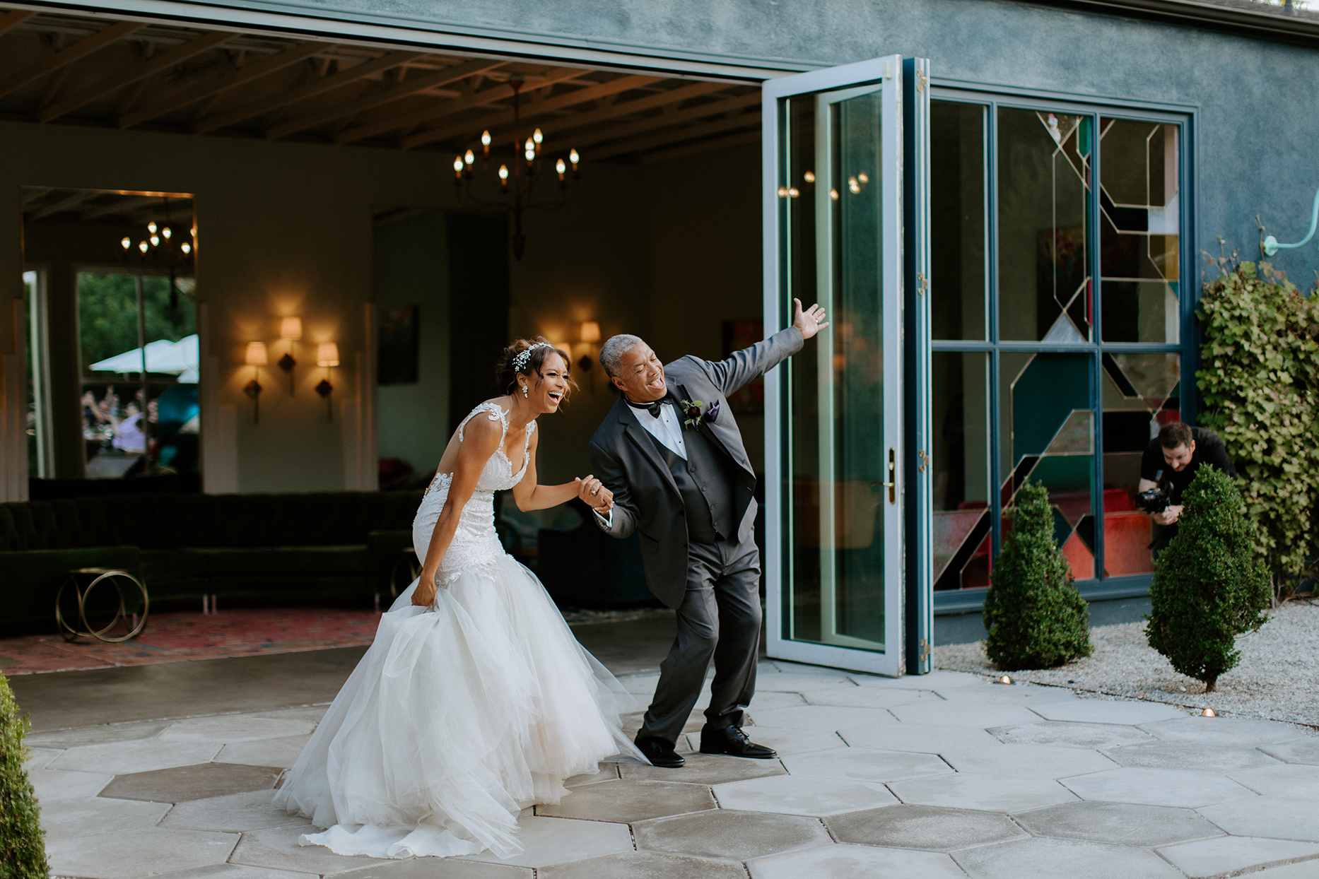 bride and father holding hands and laughing during reveal