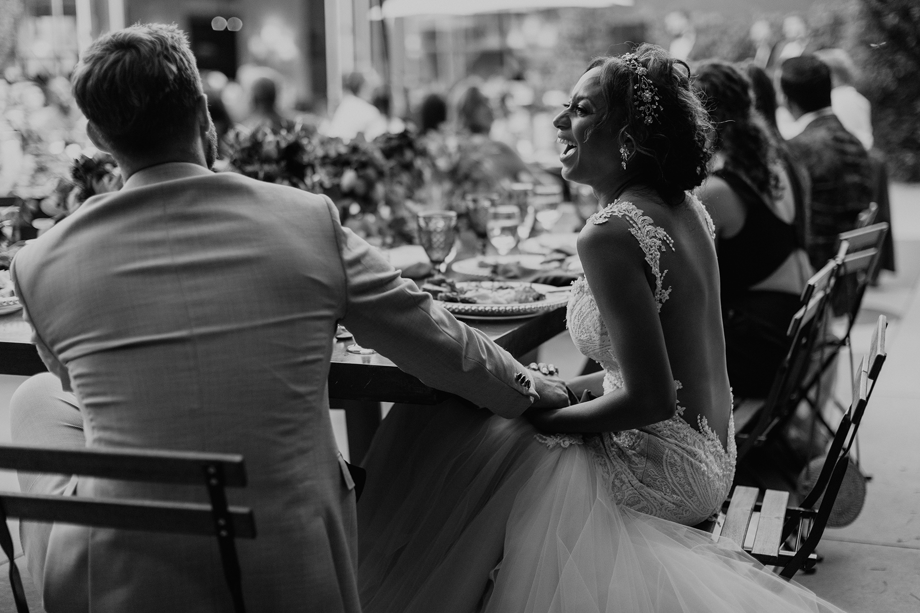 bride and groom holding hands at wedding table during speeches