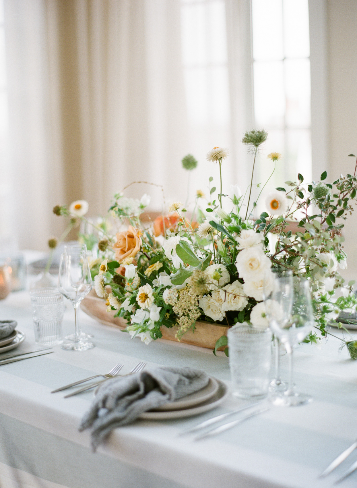 white and orange floral centerpieces on pale blue tablecloth