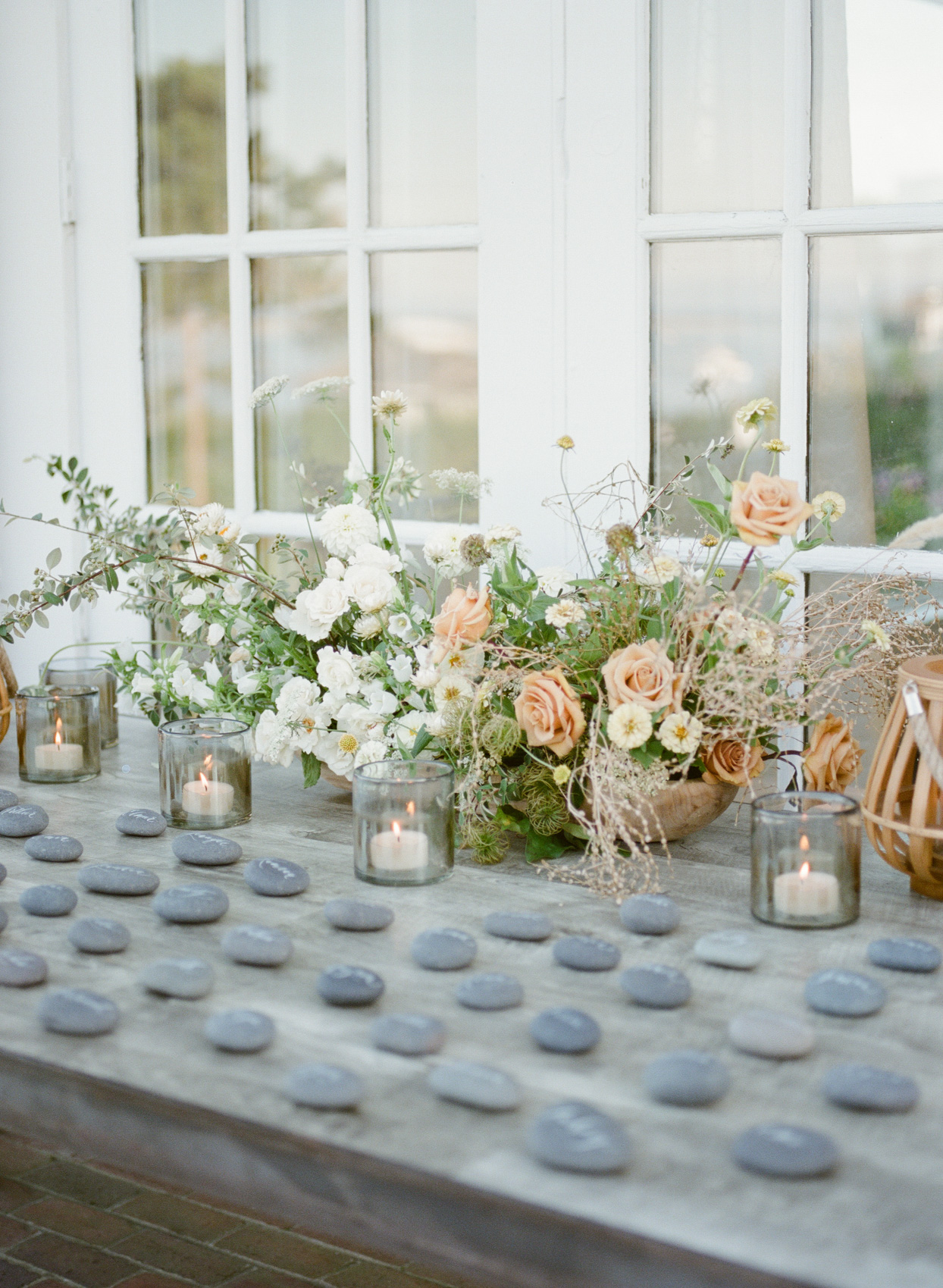 wooden table with rock escort cards, candles, and floral bouquets