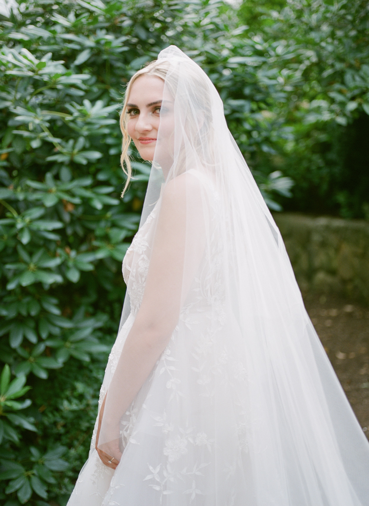 wedding bride side portrait in white in front of greenery wall
