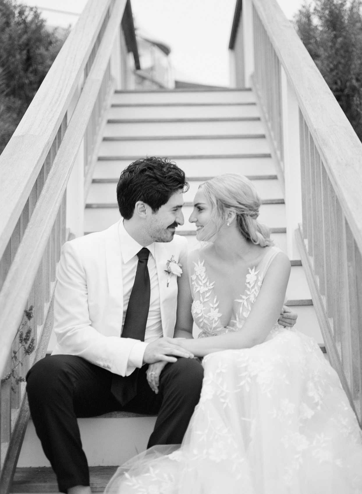 wedding couple smiling at each other sitting on steps