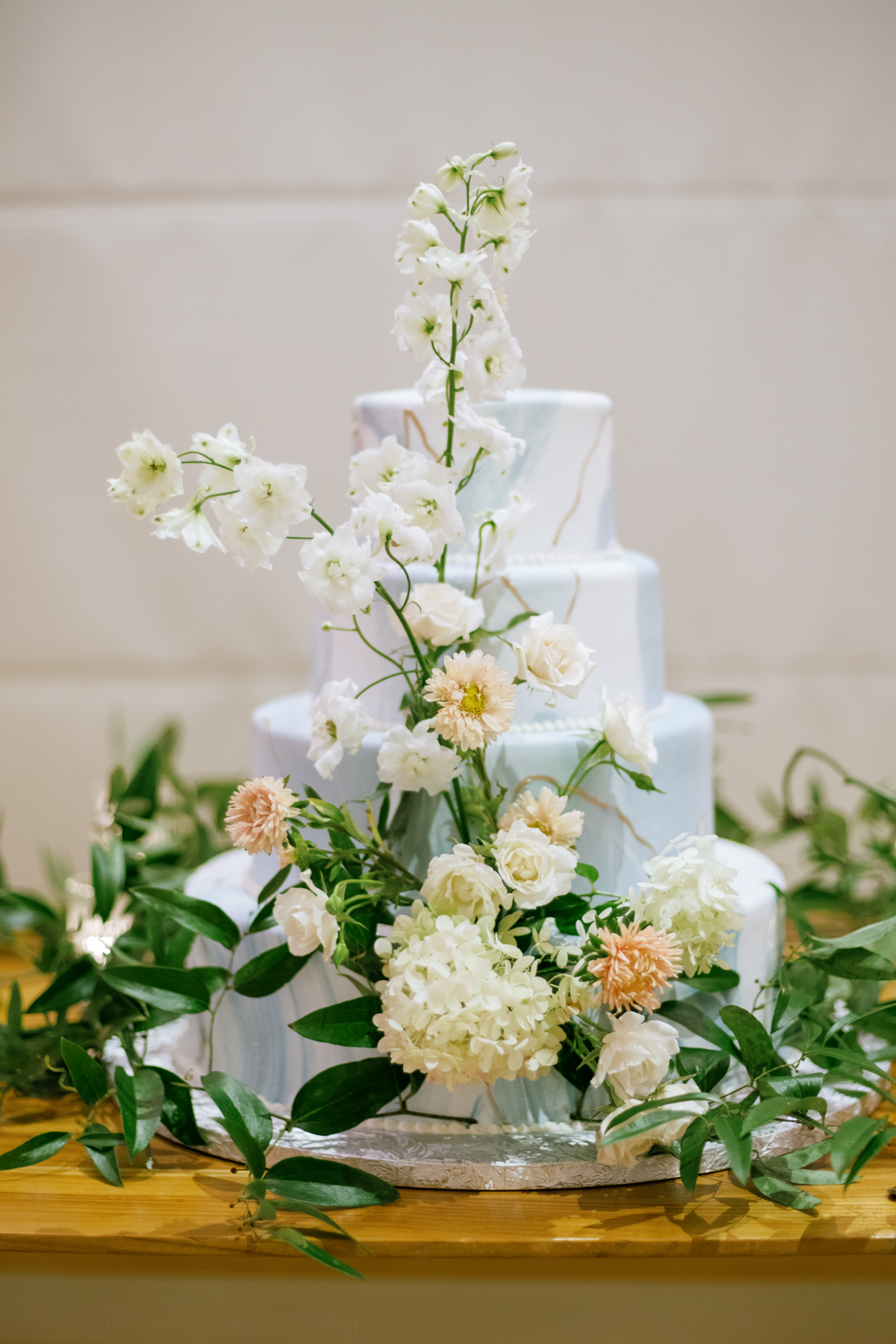 elegant blue and white wedding cake with floral decorations