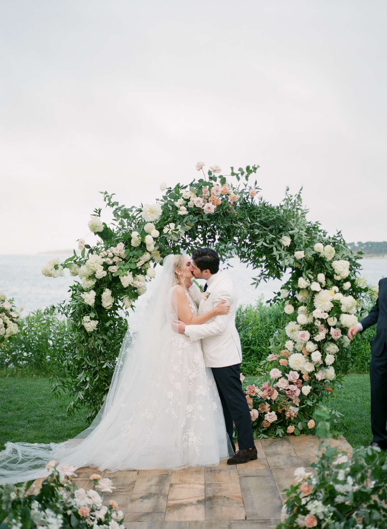 wedding couple kissing in front of floral arch by the cape