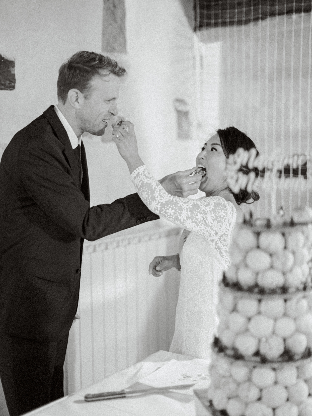 bride and groom feeding one another cream puffs