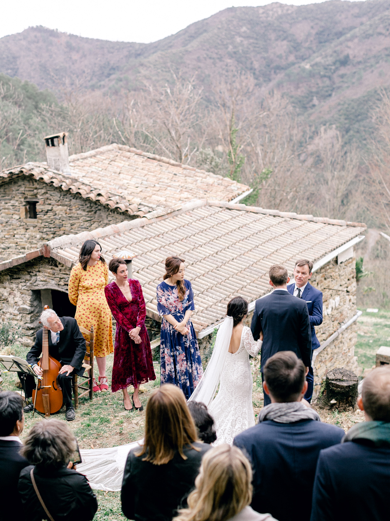 guests standing and viewing wedding ceremony on french hillside