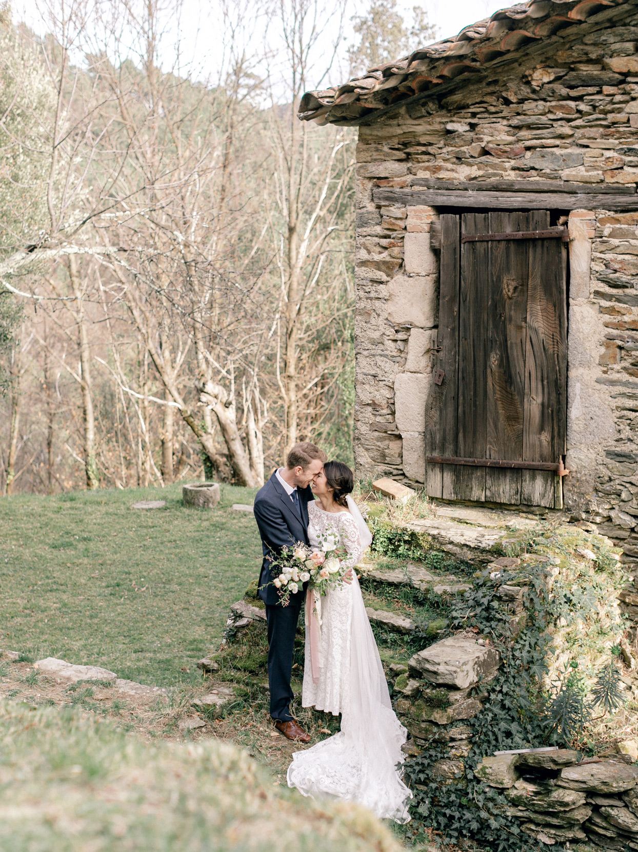 bride and groom embracing in front of small farmhouse