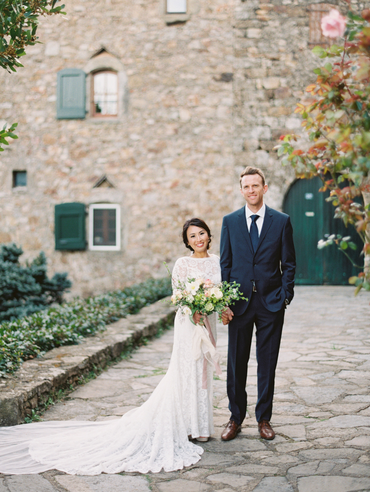 bride and groom posing in front of french countryside property