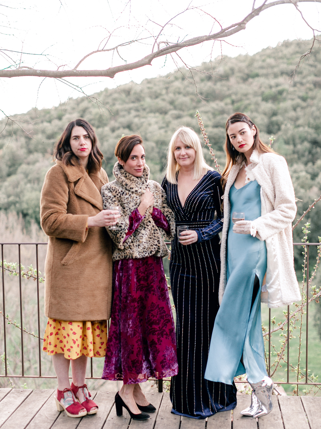 fashionable women wedding guests posing in front of hillside