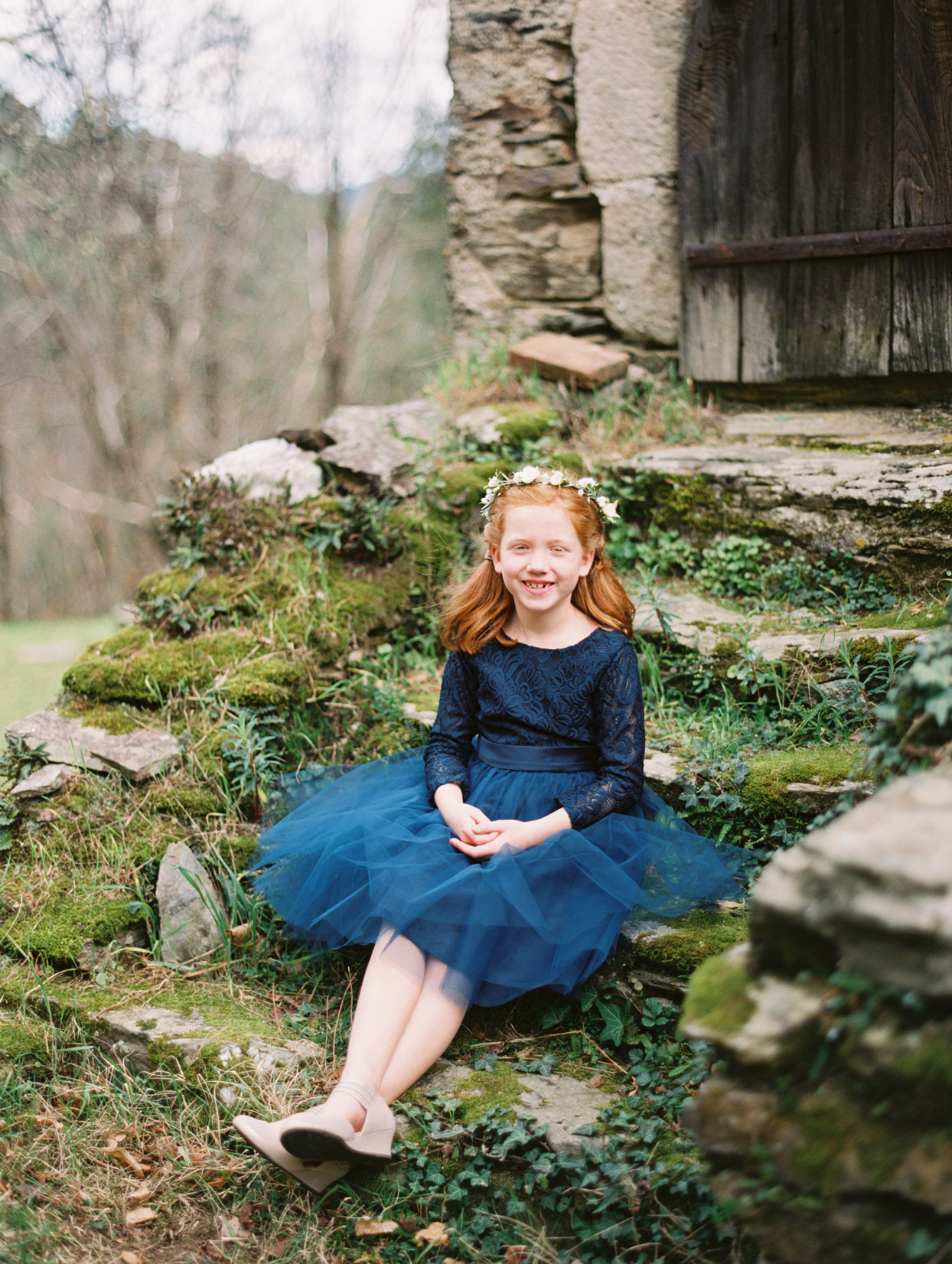 flower girl wearing navy dress with long lace sleeves and flower crown