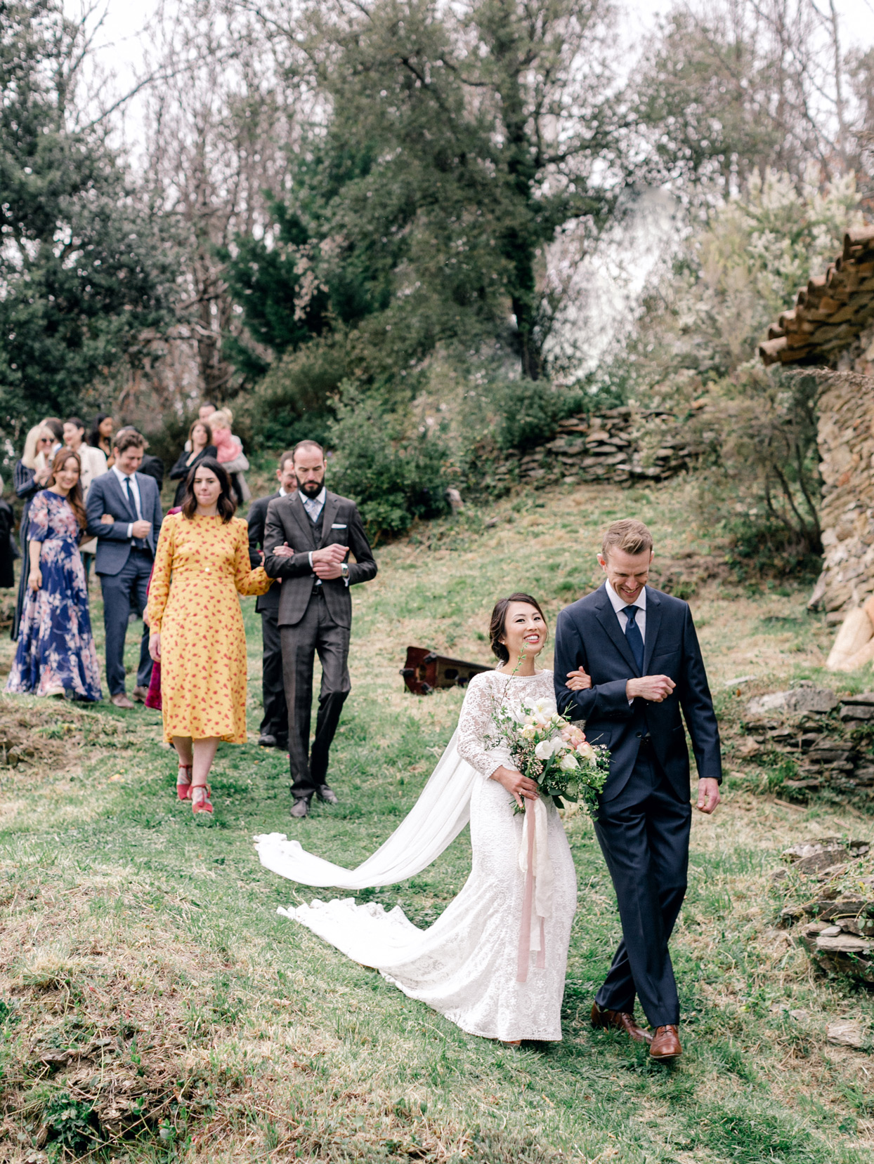 bride and groom leading wedding guests down hillside