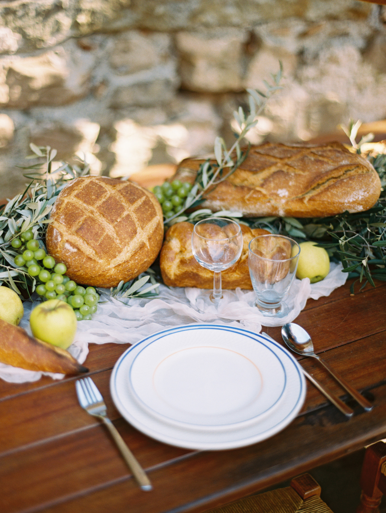 wedding reception tablescape adorned with bread fruit and olive branches