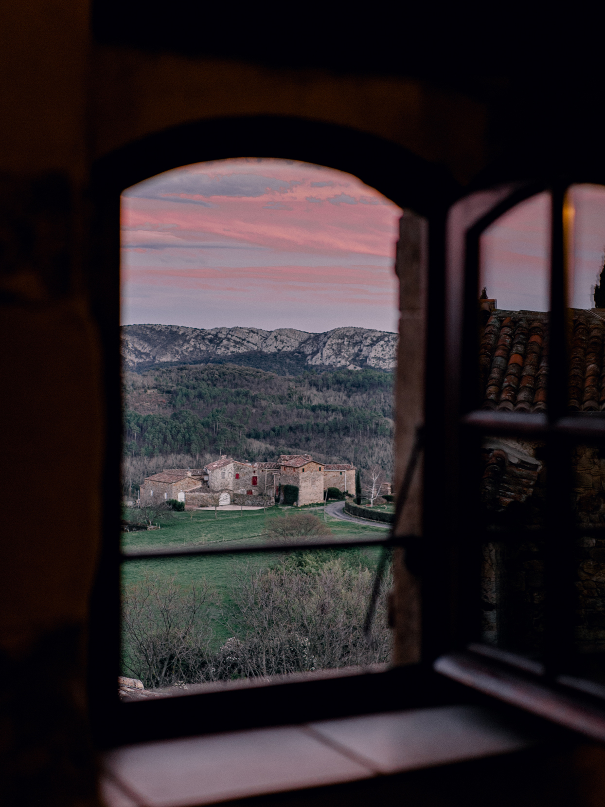window overlooking sunset of french country hillside
