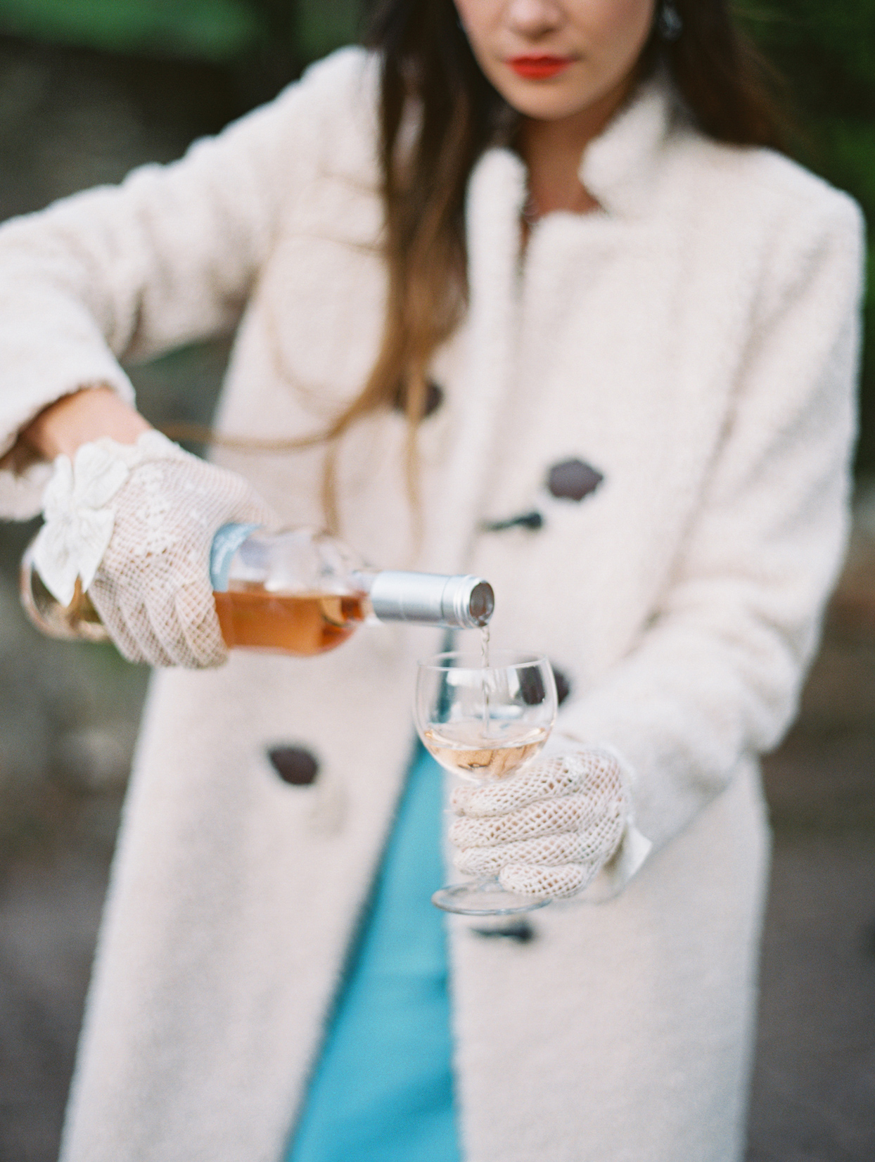 woman wearing white gloves pouring glass of wine