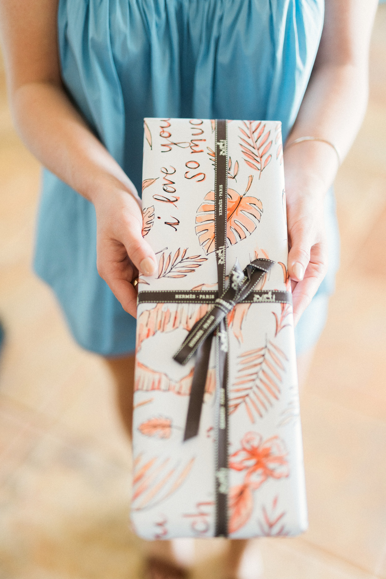 woman holding gift wrapped in custom paper for wedding