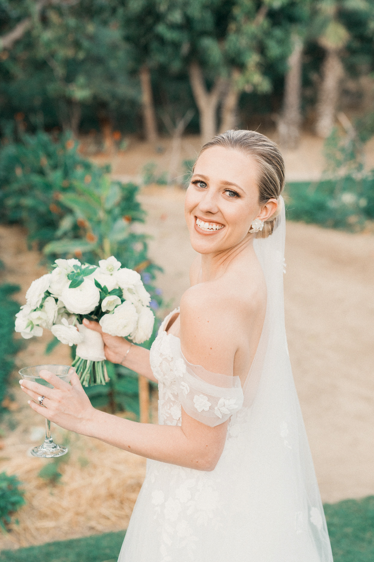 bride in white dress holding champagne and wedding flowers