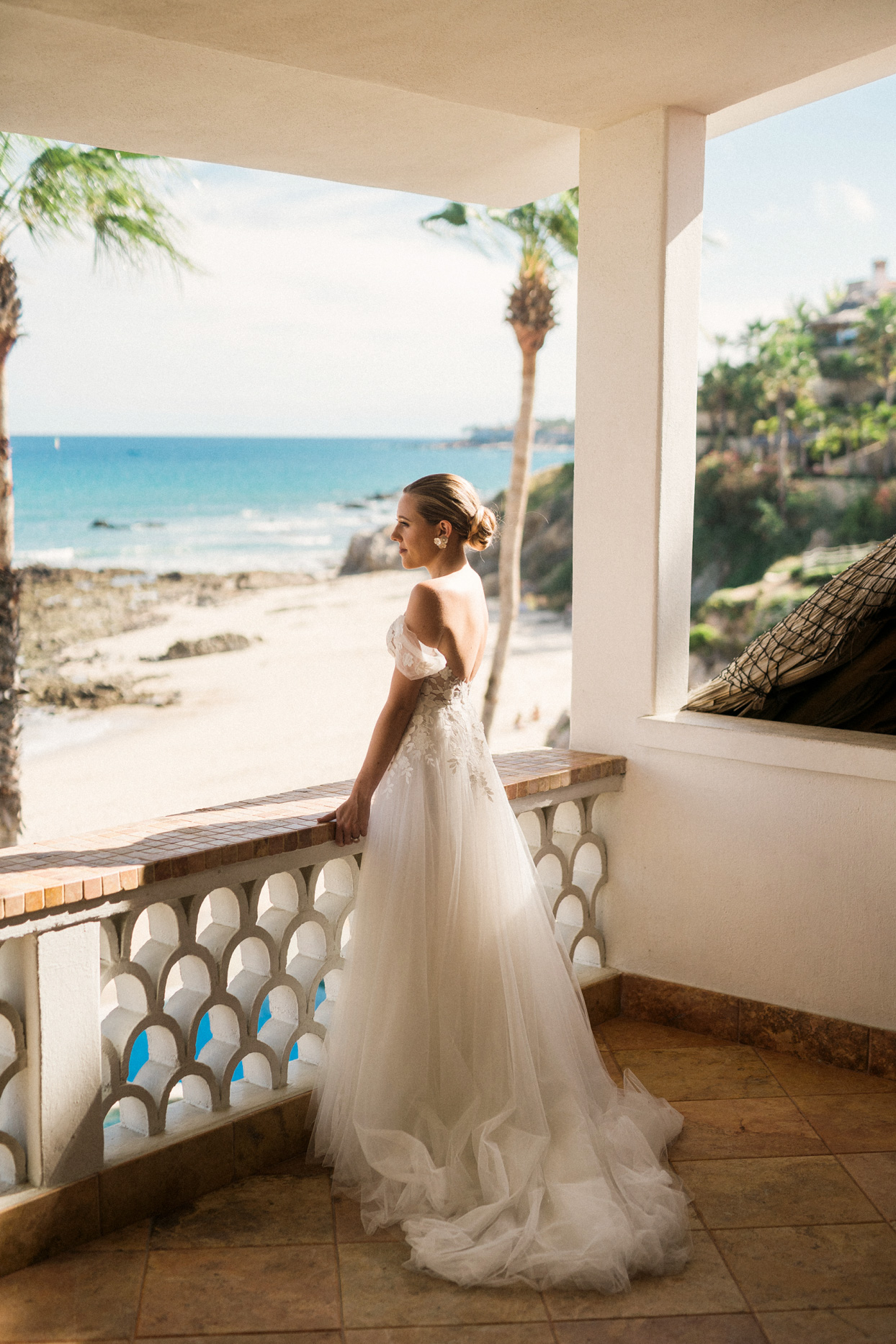 bride gazing out at beach standing on mexican balcony