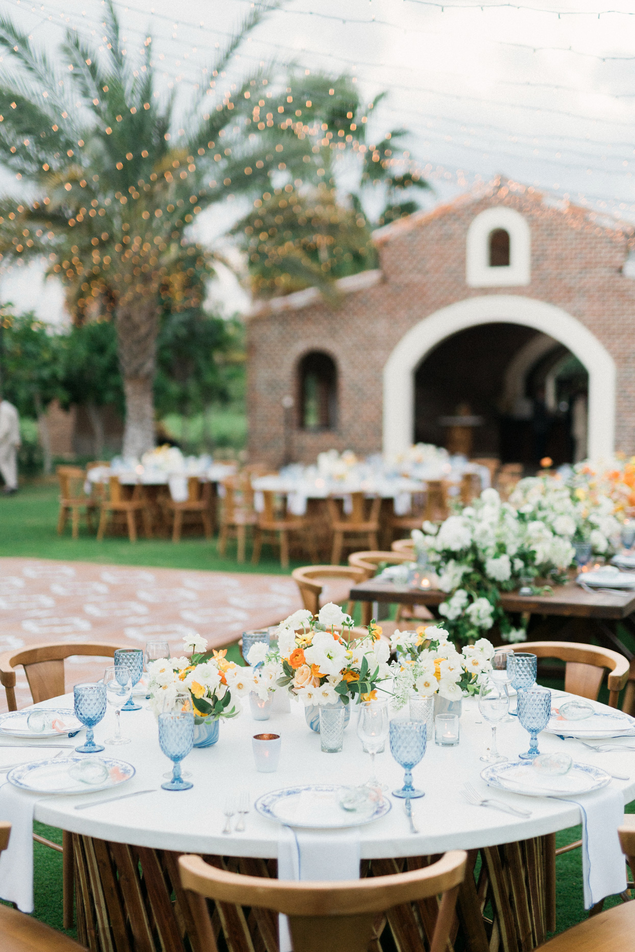 outdoor wedding tables with orange, white and blue floral decor