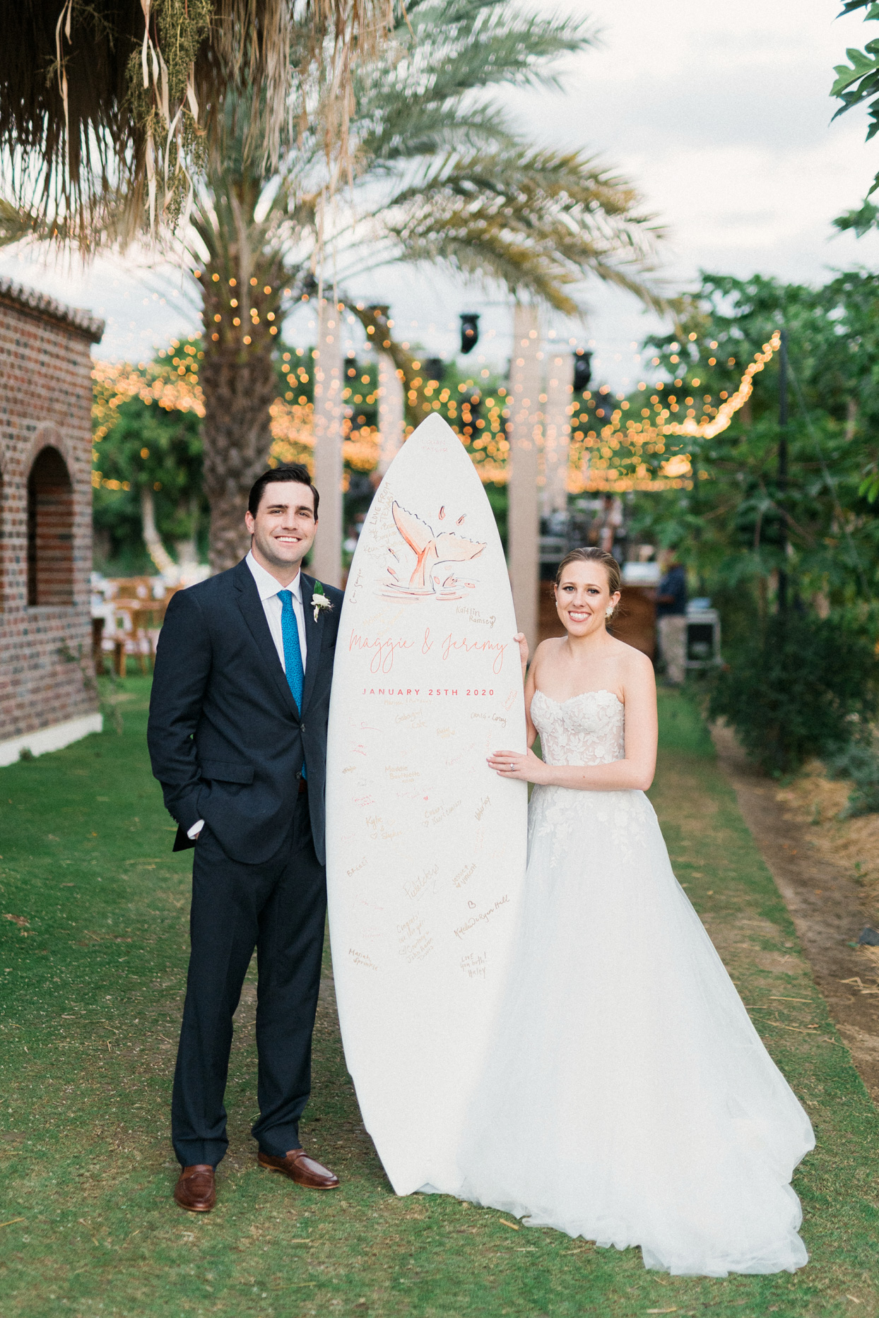 bride and groom posing with guest book surf board