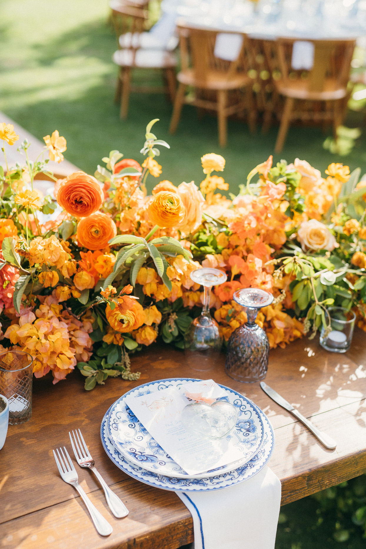 elegant wedding place setting with ornate blue plates and orange florals