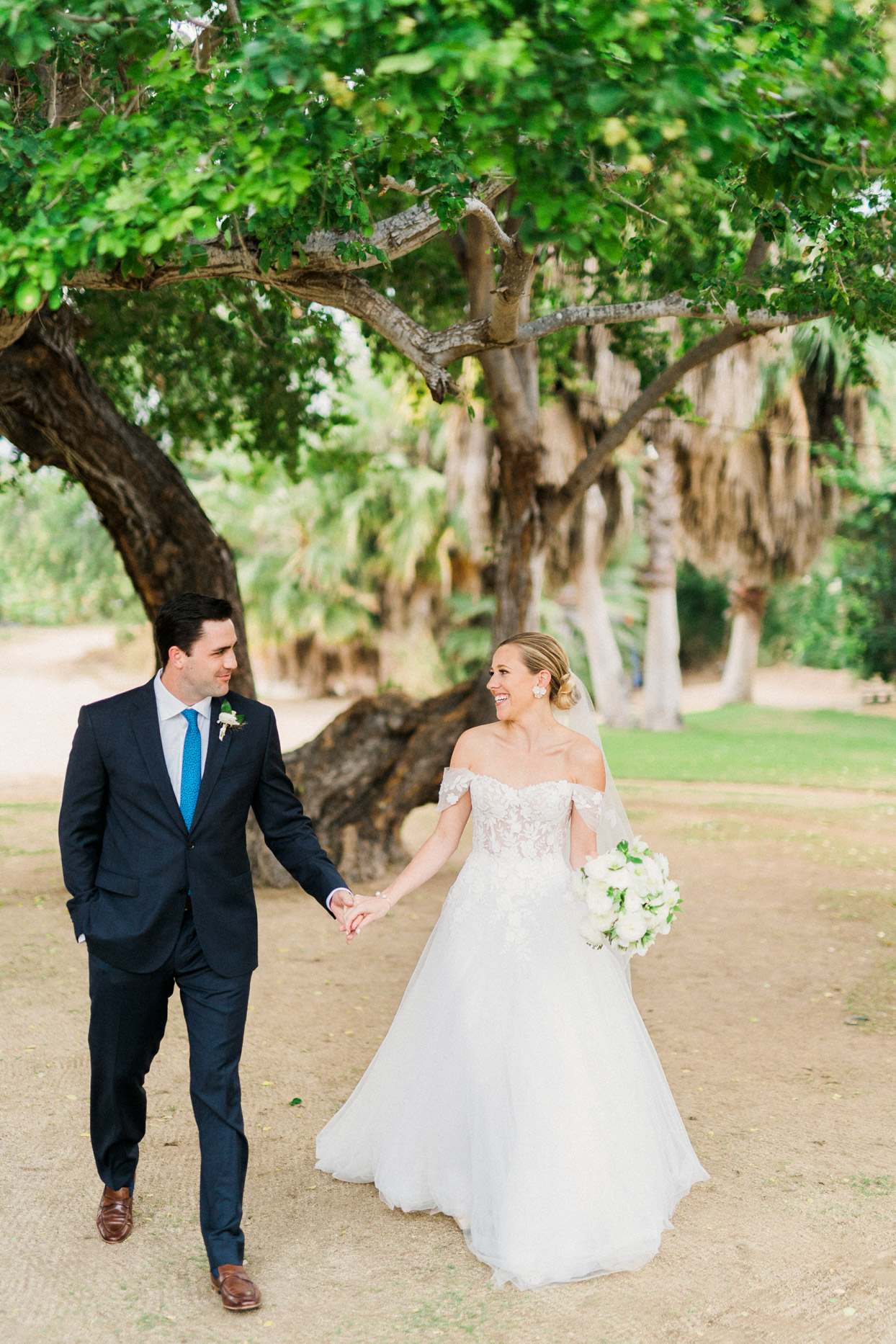 wedding couple holding hands and walking along sand