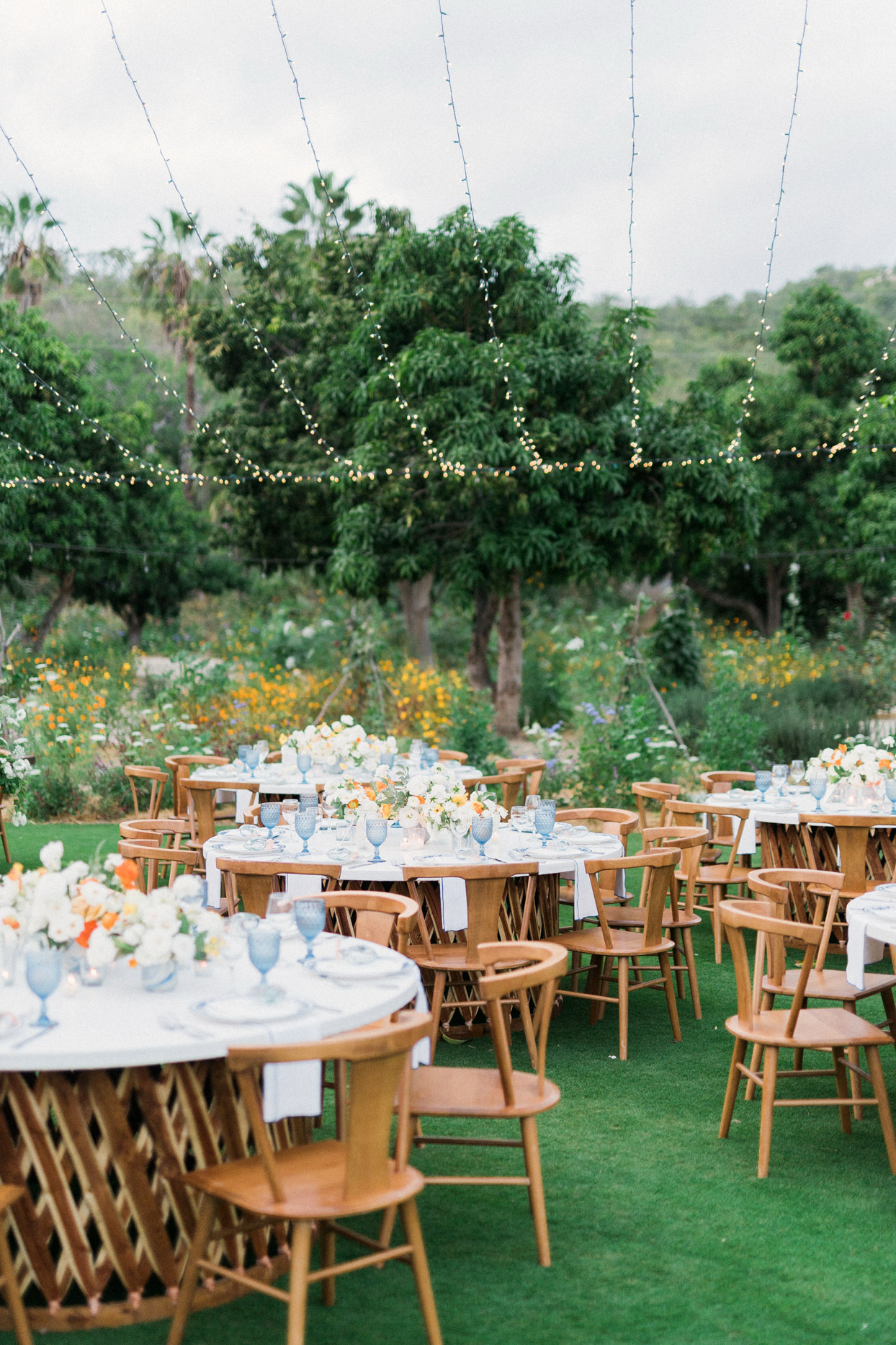 round wooden tables with marble tops for outdoor reception