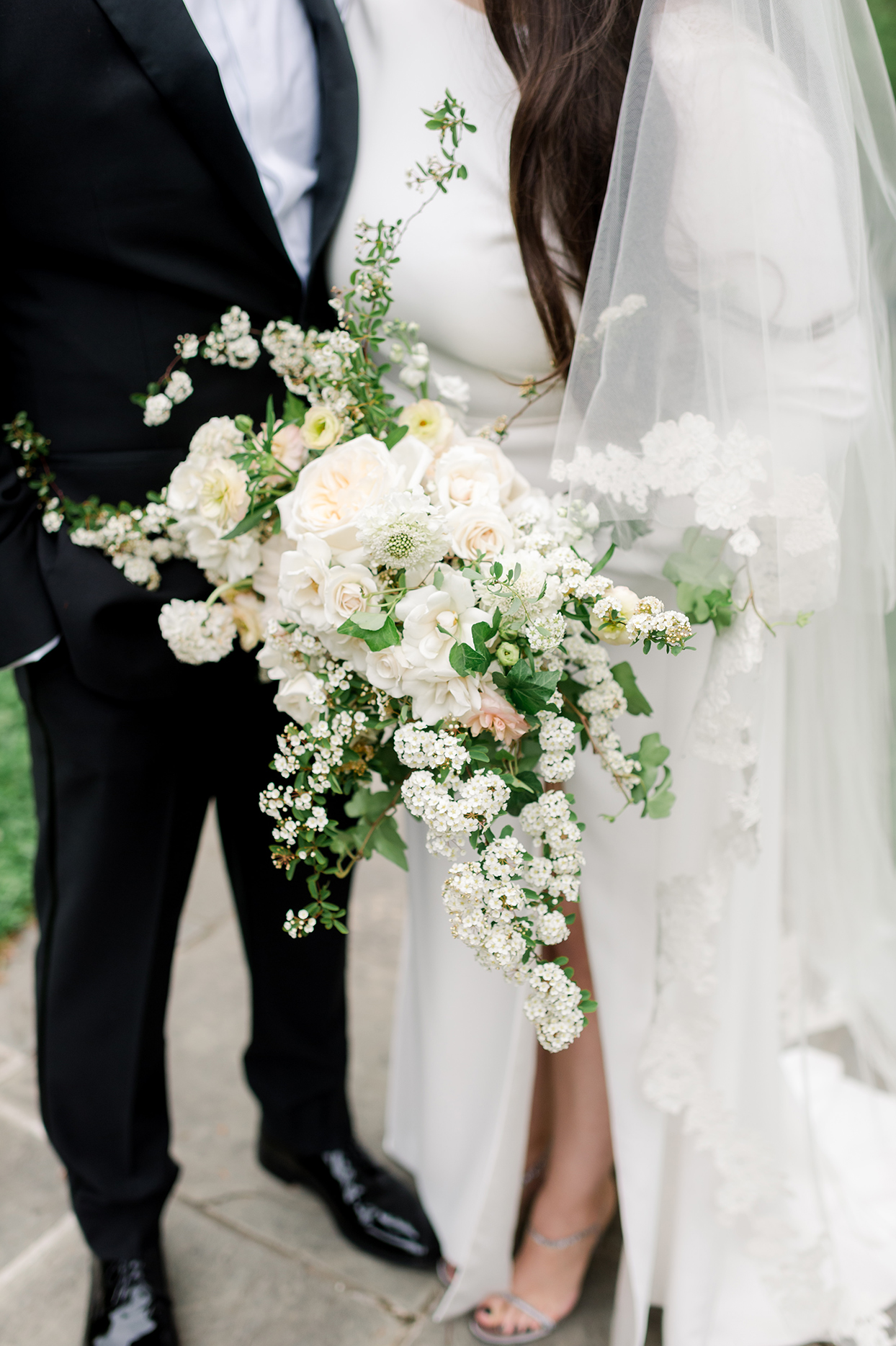 Bride's bouquet of spirea, garden roses, spray roses, scabiosa, and butterfly ranunculus