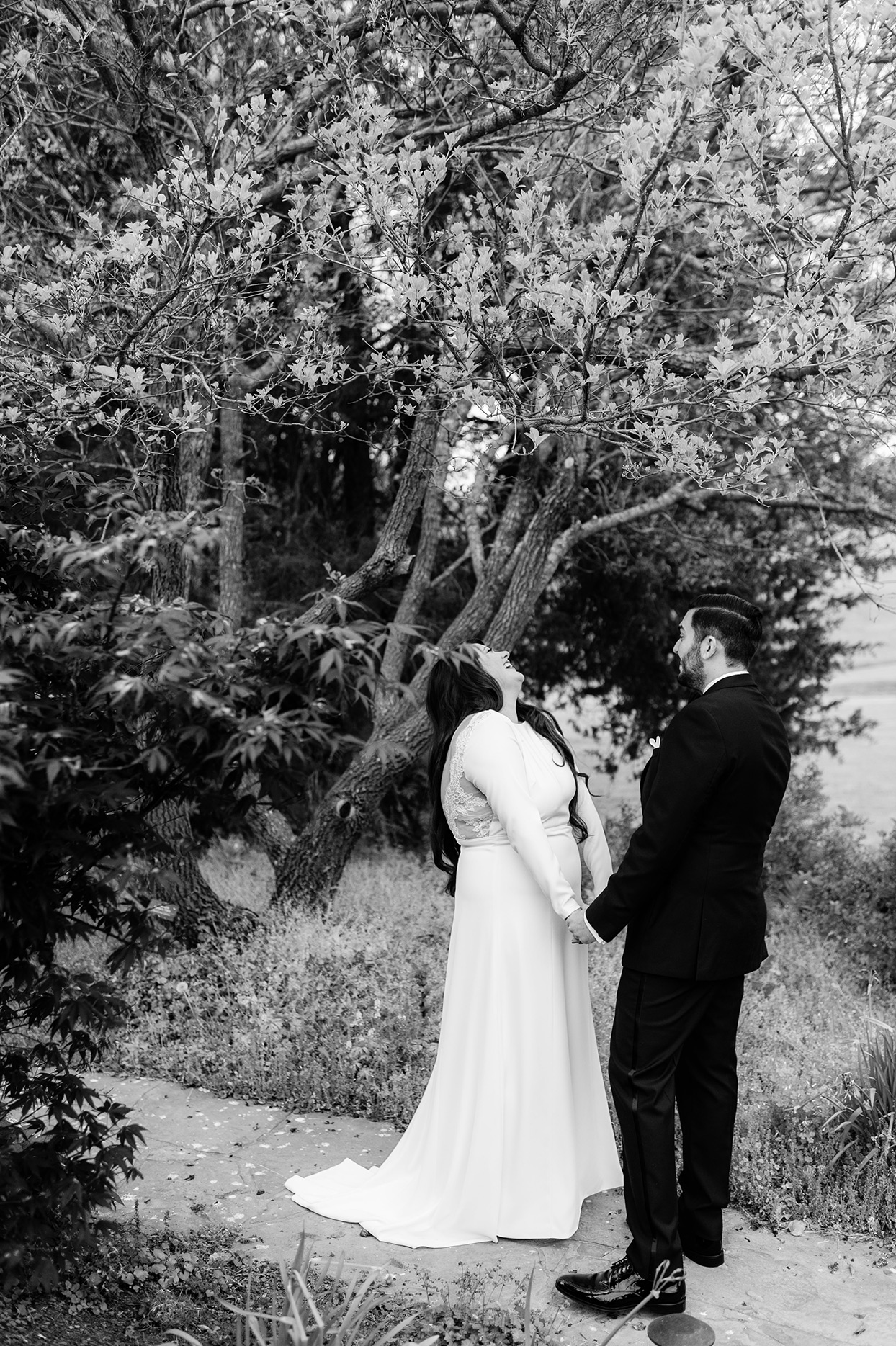 Bride and groom laughing together in garden