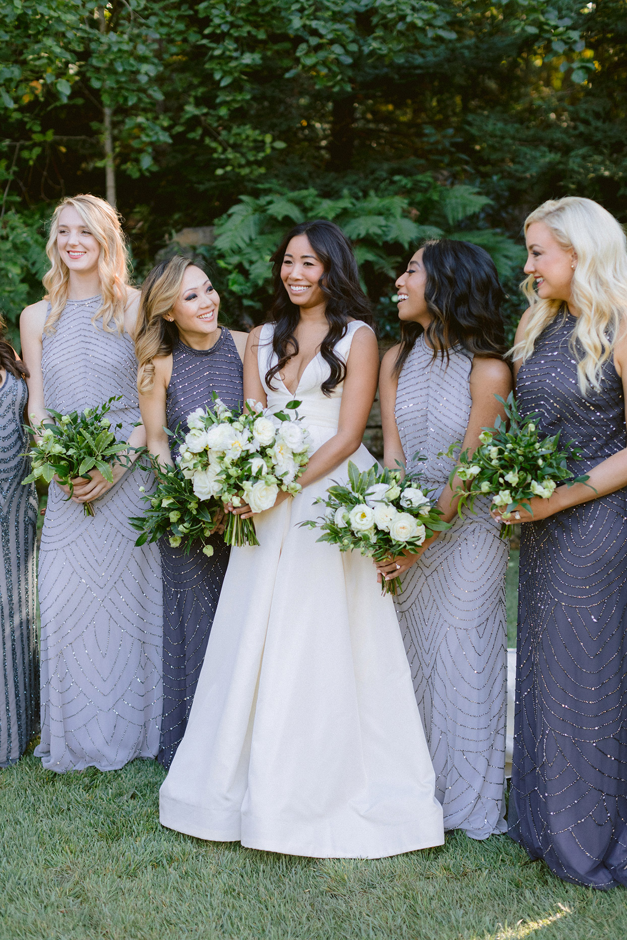 Bridesmaids in BHLDN Anthropologie dresses and bouquets of jasmine, viburnum, and gardenia