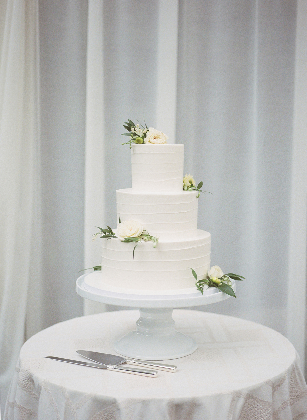 Wedding cake with white butter cream, stripes, and flower accents