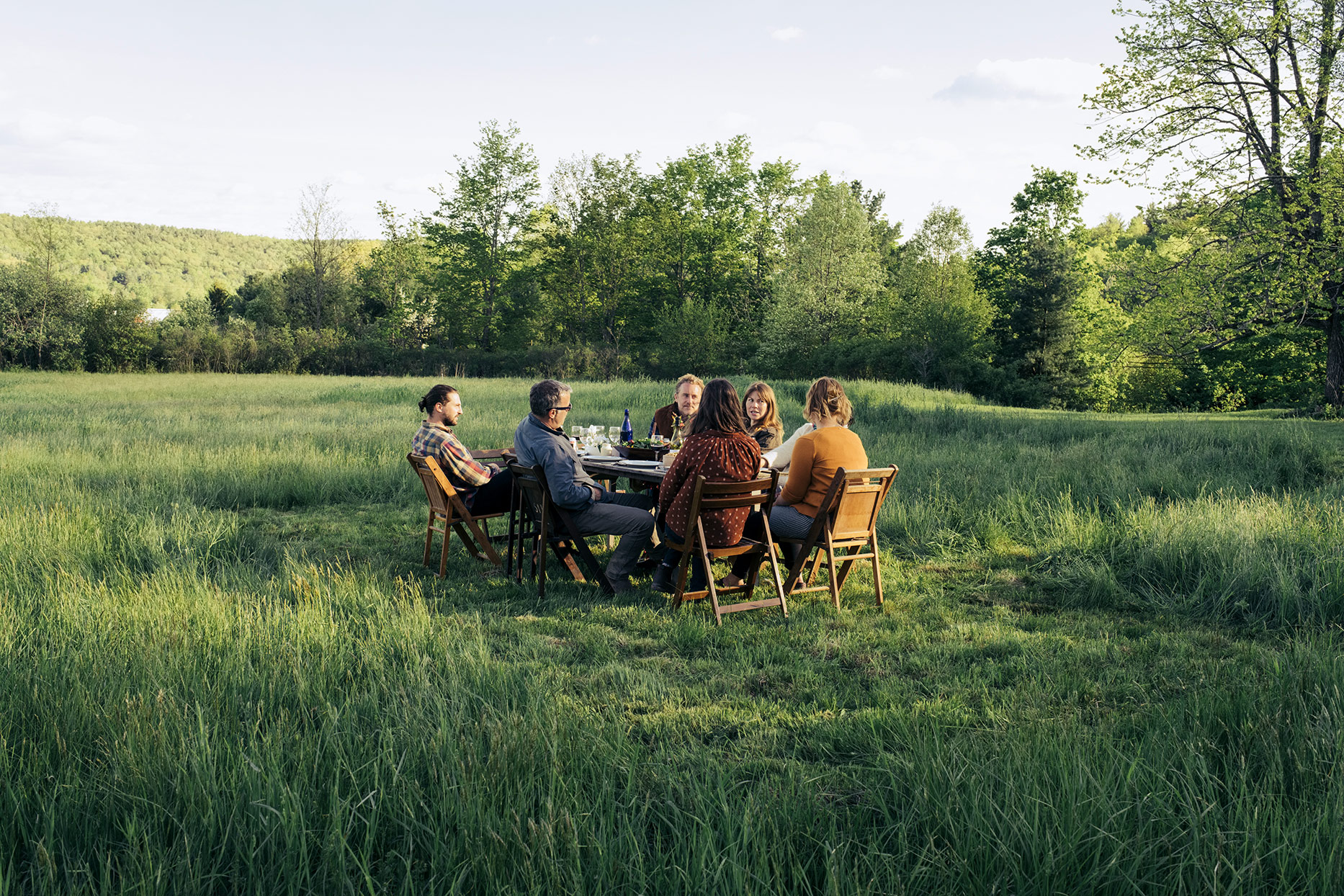 guests sitting at table for dinner party in field