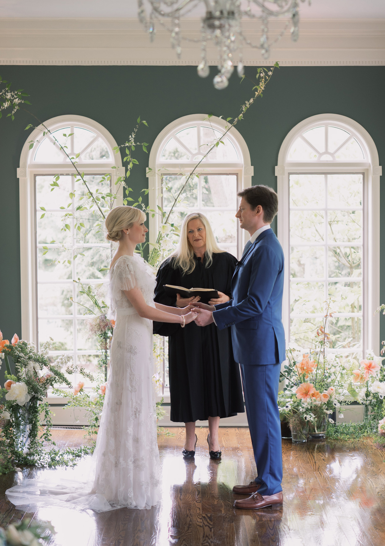 couple exchanging vows in intimate house ceremony surrounded by flowers