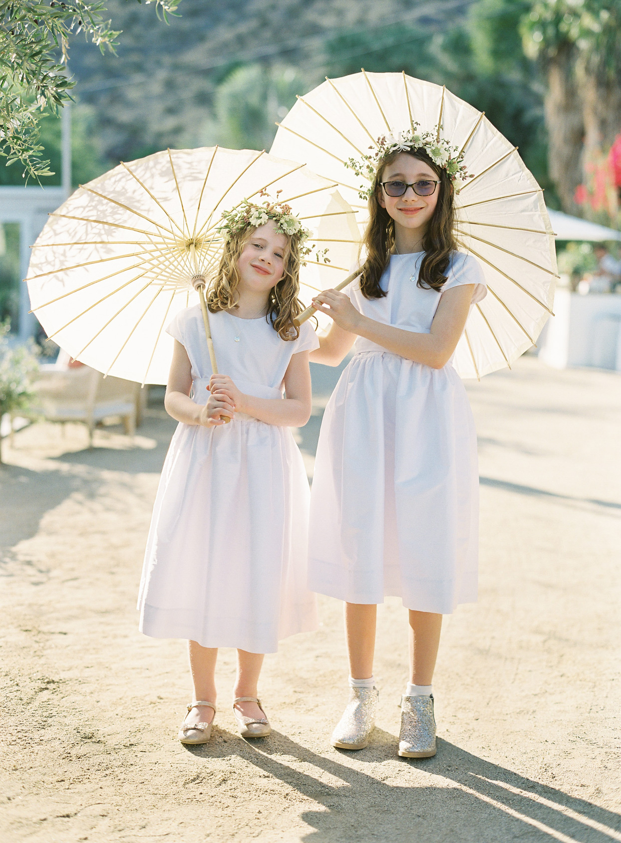 wedding flower girls holding parasols in the sun