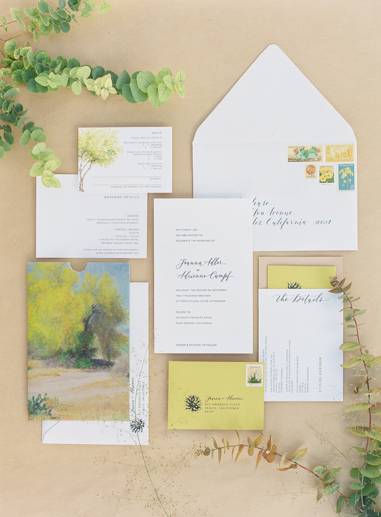 yellow and white wedding invitation suite with greenery