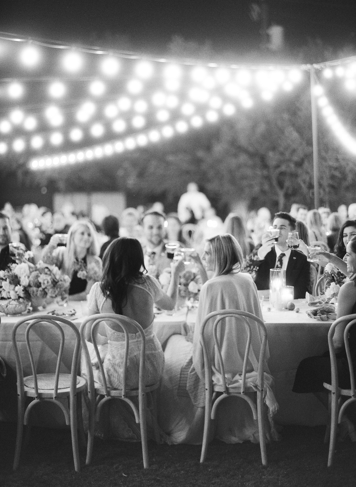 brides and guests toasting at wedding reception dinner