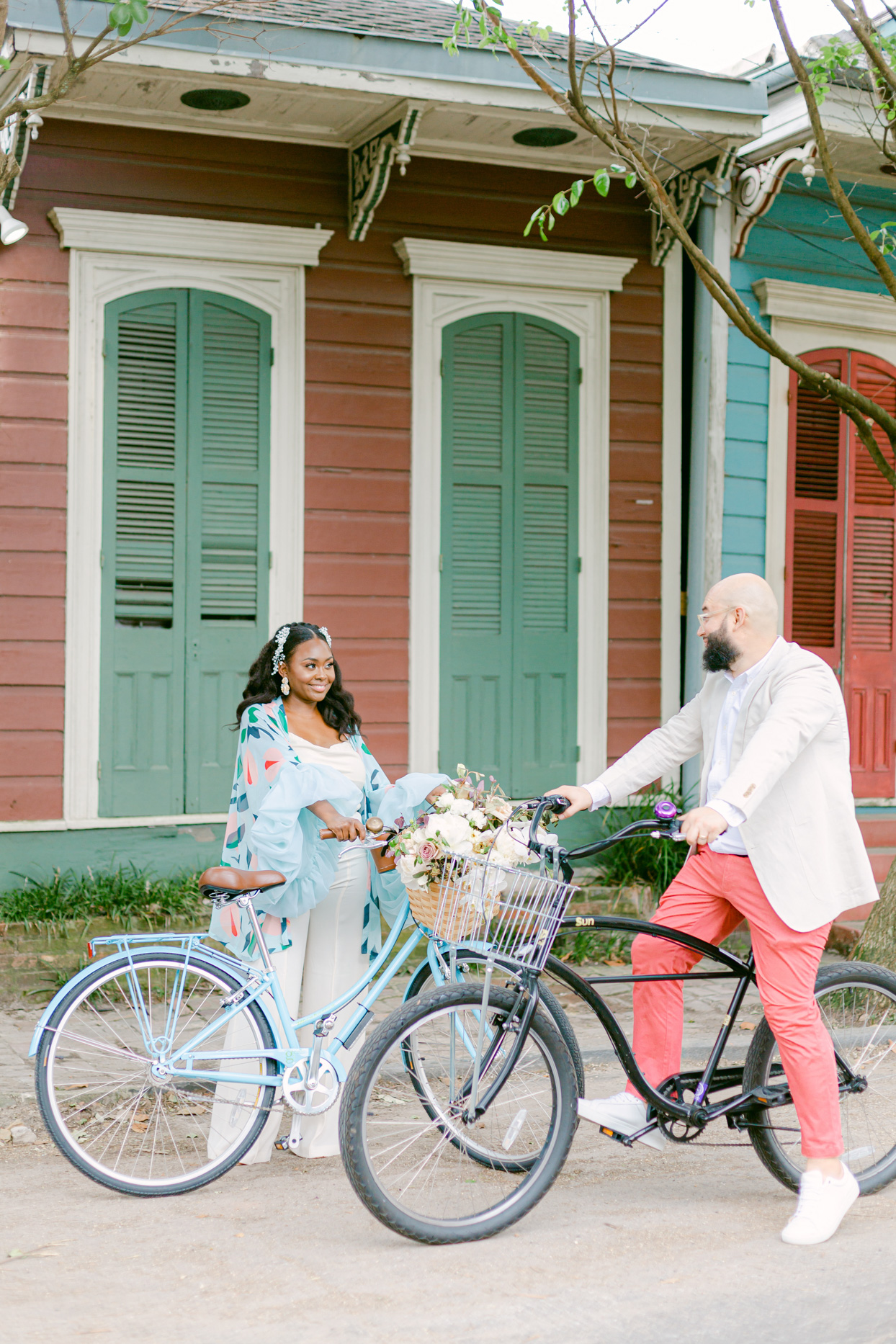 couple wearing pastels with bikes in front of colorful building