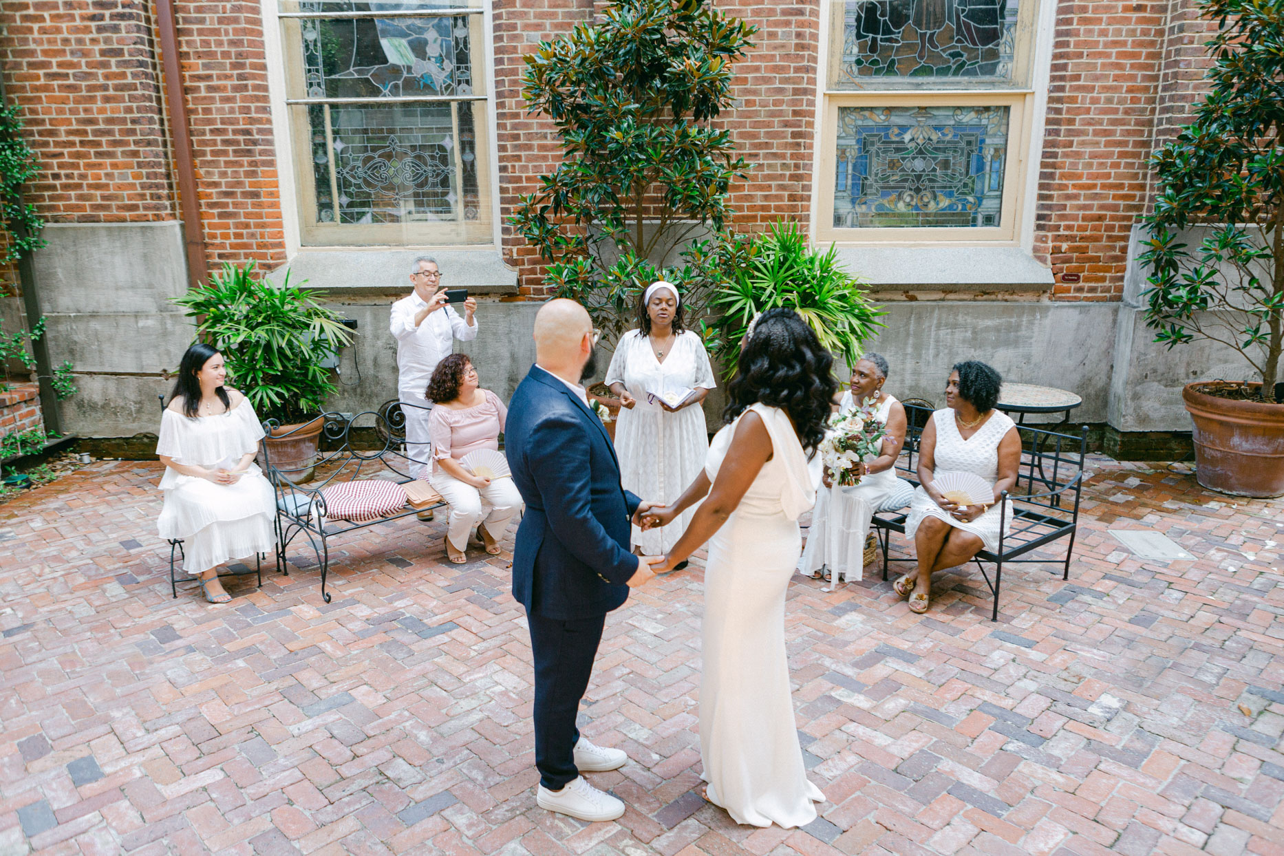 wedding couple during socially distanced ceremony in brick courtyard