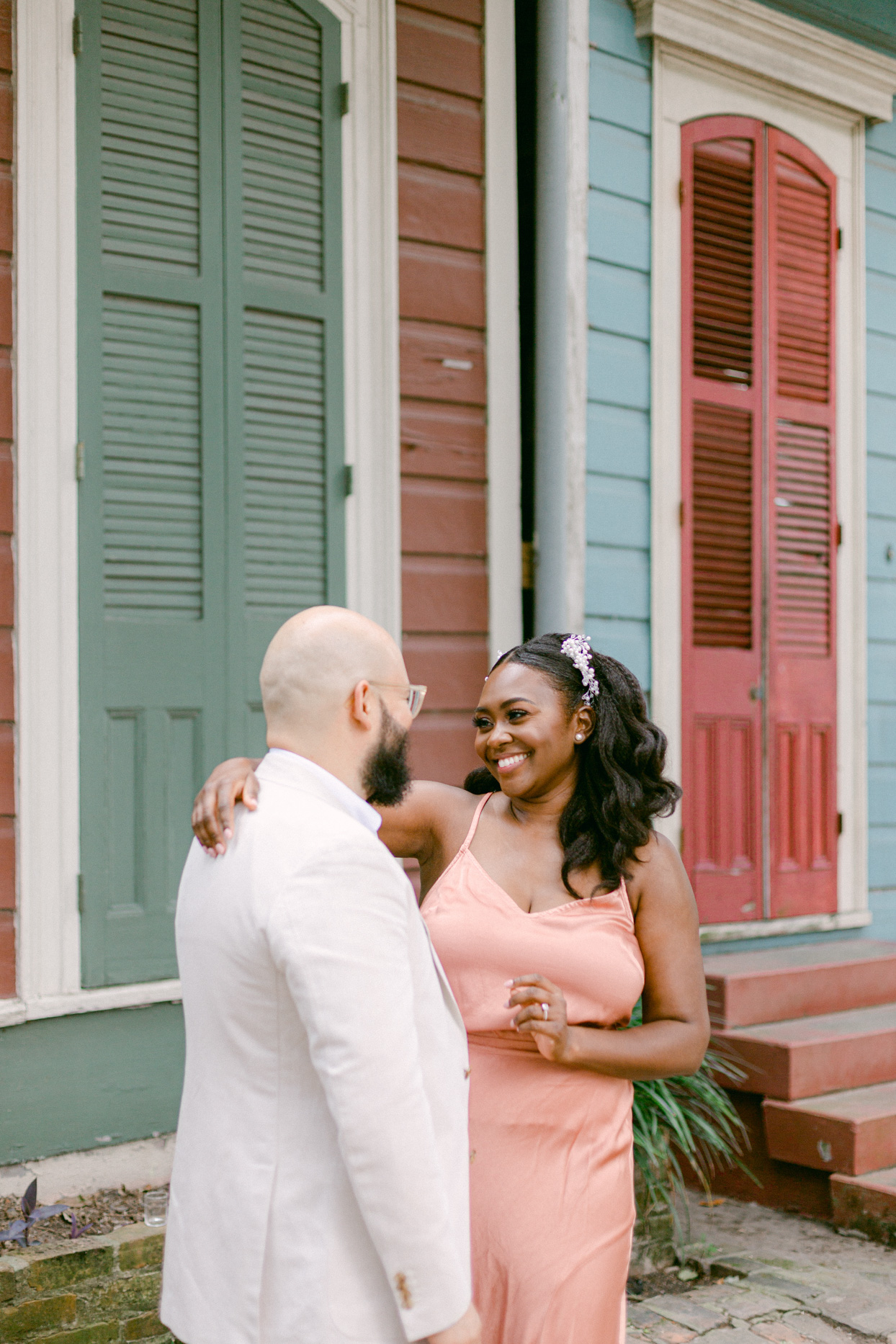 wedding couple smiling at each other in front of colorful house